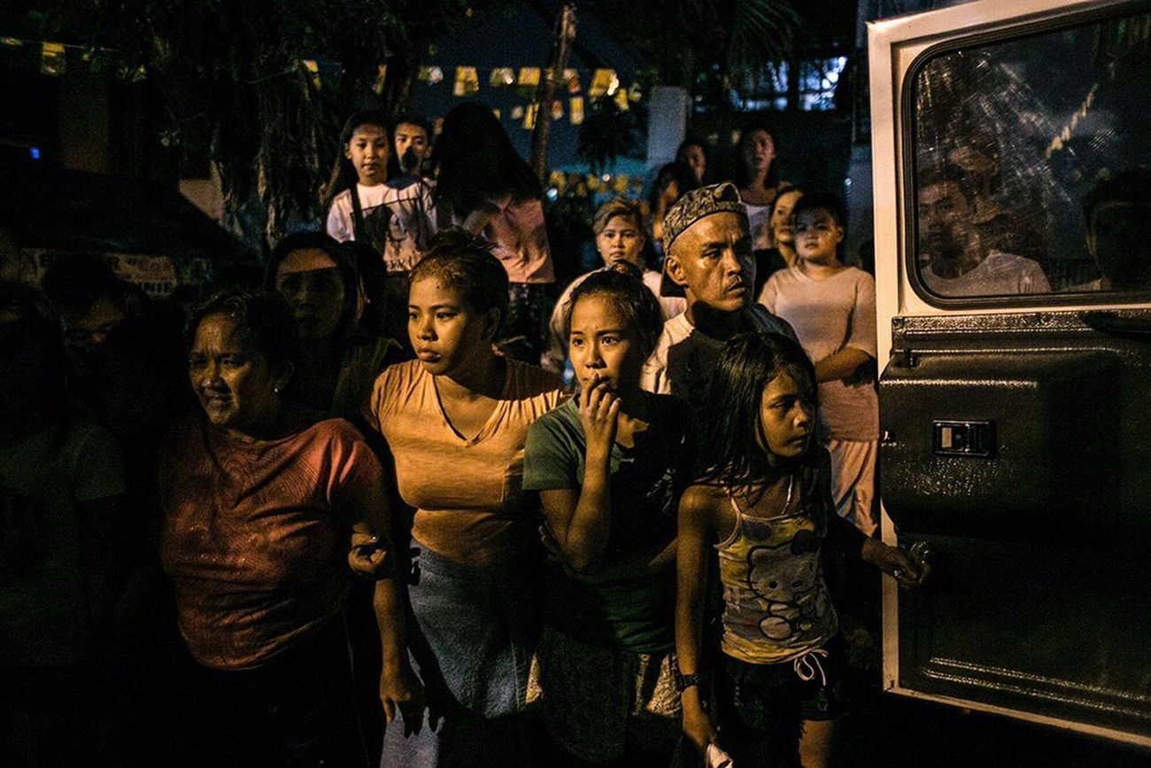 The Photojournalist - 2017 EyeEm Awards Neighbors watch funeral workers carry the body of one of an alleged pusher killed during a shootout with policemen in Caloocan City. Most Filipinos believe President Duterte can fulfill his promises based on national surveys. Months after his victory in the presidential derby, blood and tears continue to flow in the streets and alleys-- and there's no sign of stopping. Human rights group expressed alarm over the snowballing incidence of so called extra judicial killings of suspected 'drug' criminals.