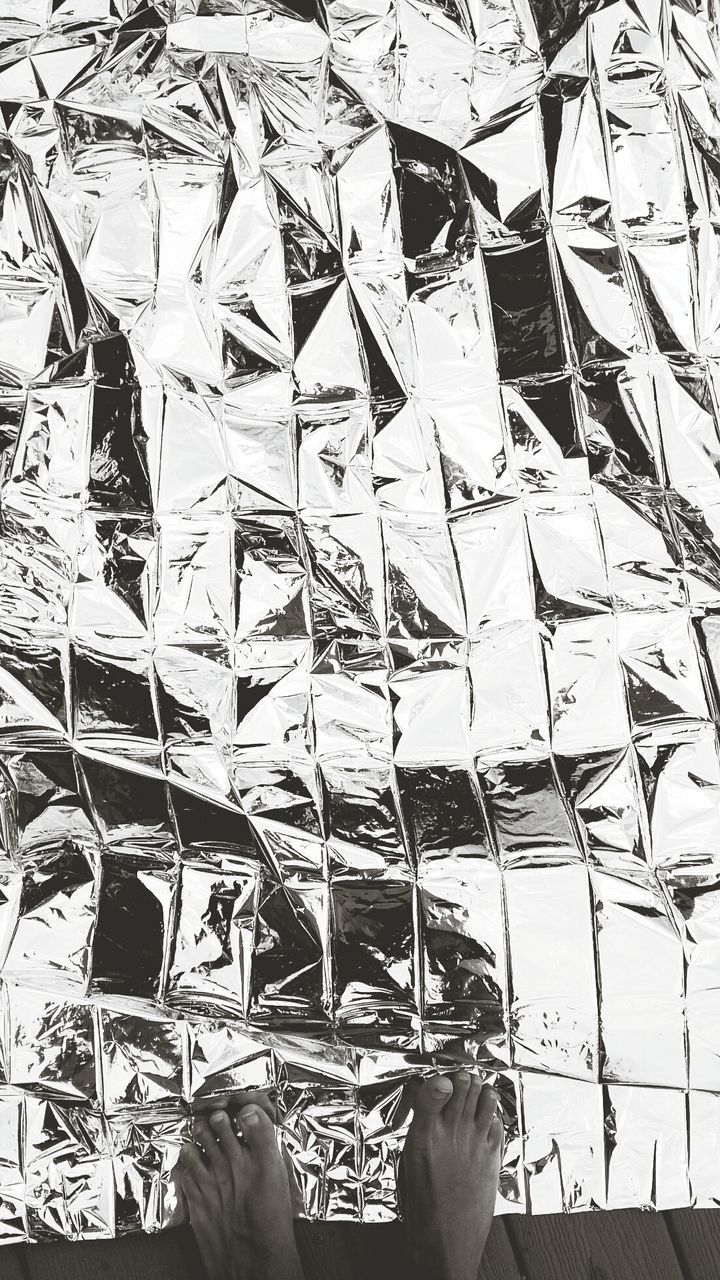 Low Section Of Person Standing By Foil Paper On Street