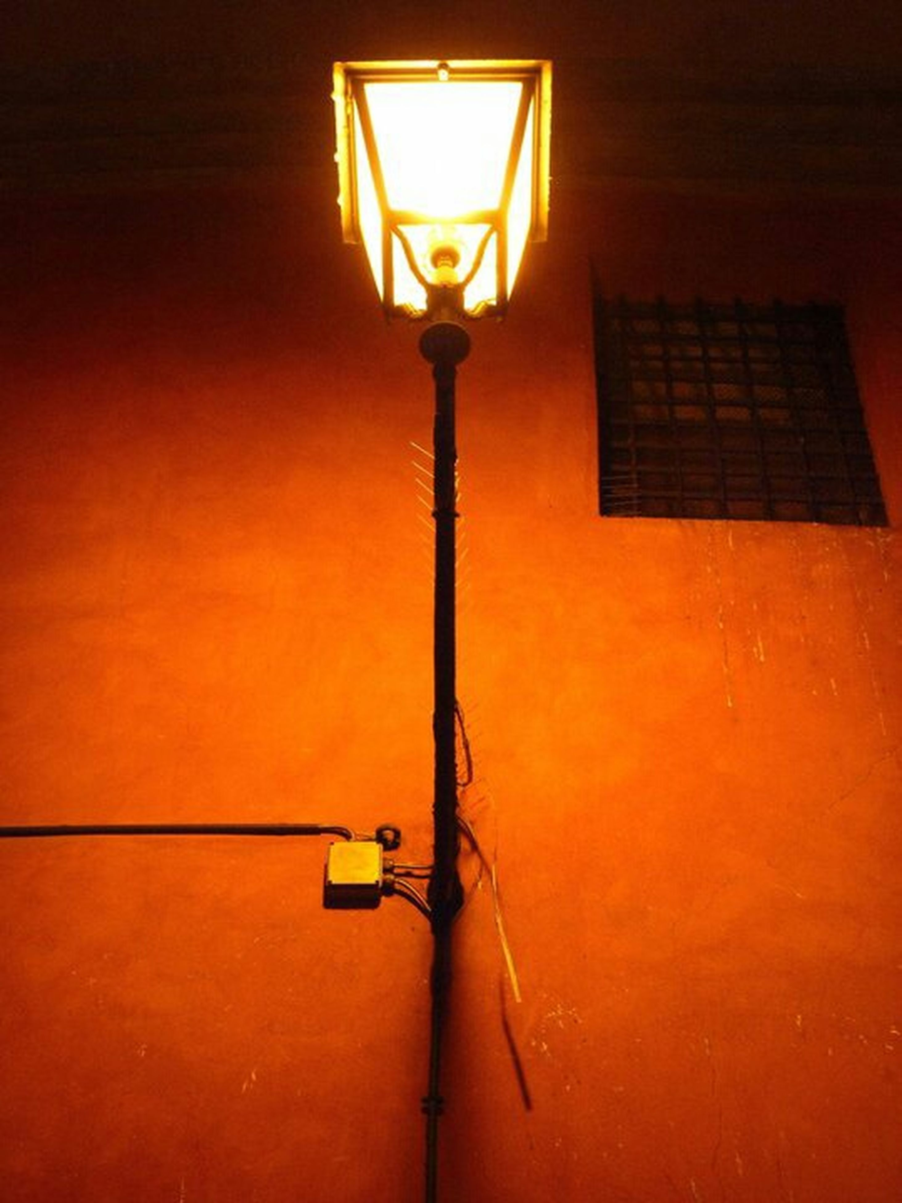 lighting equipment, illuminated, built structure, architecture, street light, wall - building feature, electric light, orange color, electricity, electric lamp, lamp, yellow, low angle view, indoors, lantern, building exterior, wall, hanging, door, house