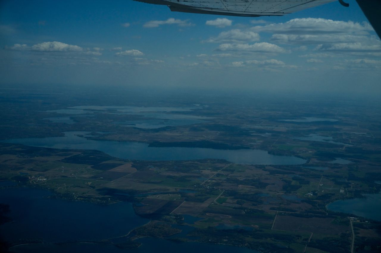 aerial view, airplane, transportation, landscape, scenics, beauty in nature, flying, air vehicle, journey, mid-air, sky, nature, mode of transport, travel, tranquil scene, patchwork landscape, cloud - sky, aircraft wing, no people, outdoors, tranquility, vehicle part, day, agriculture, airplane wing, view into land