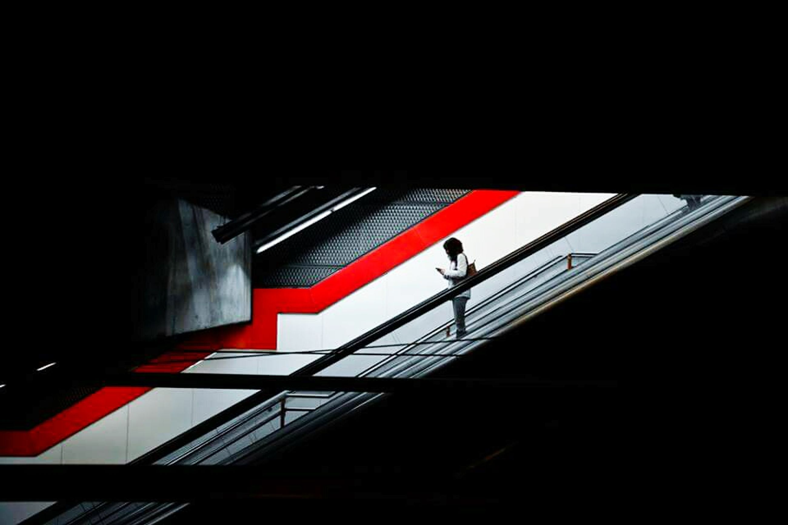 steps and staircases, railing, steps, built structure, staircase, indoors, architecture, low angle view, copy space, red, escalator, transportation, bridge - man made structure, dark, stairs, connection, sunlight, walking, men