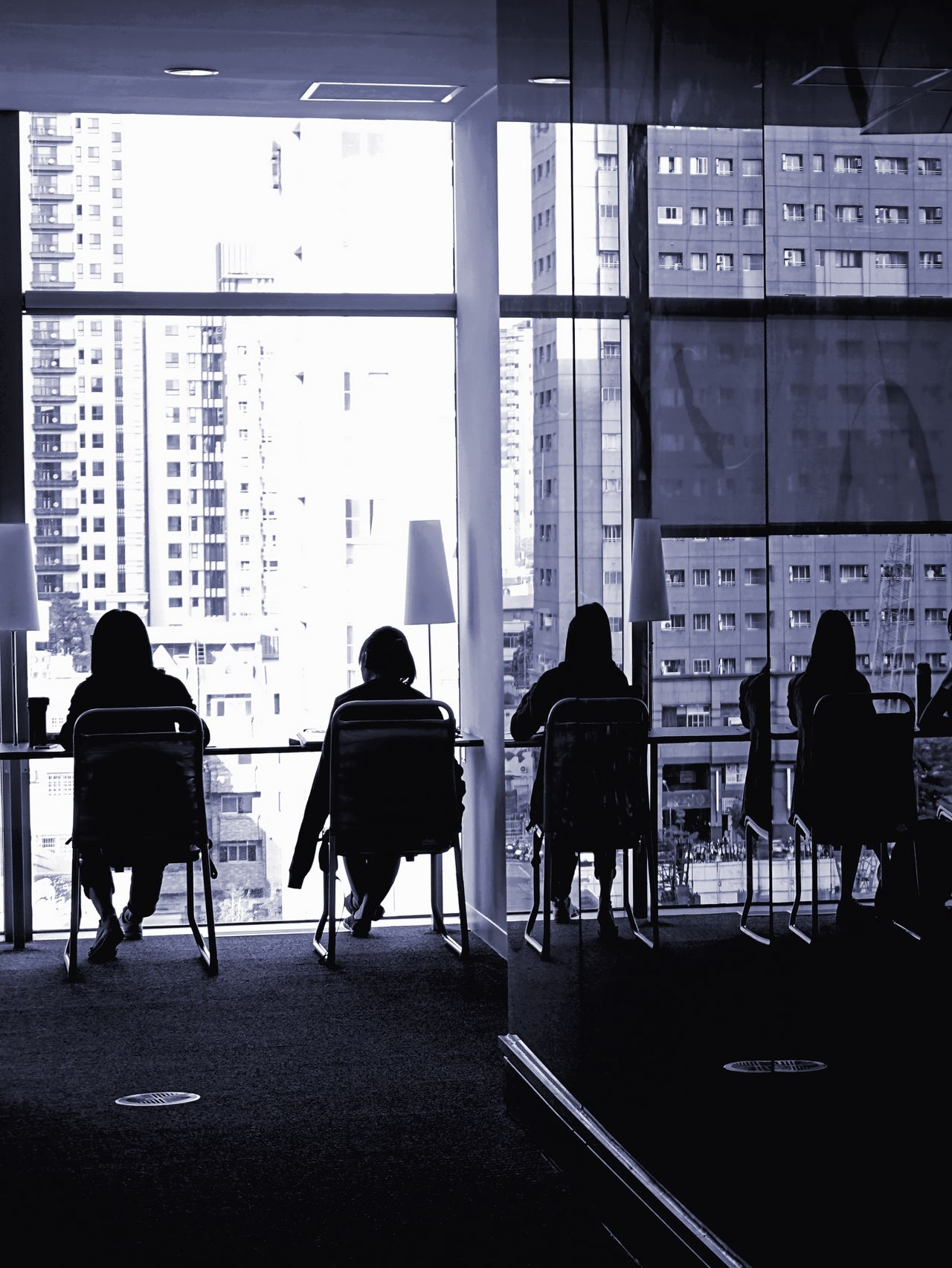 Monochrome image of outline of people reading by a large glass building facade City Life Facades Library Medium Group Of People Modern Monochrome Reading Books Silhouettes Students Studying Hard
