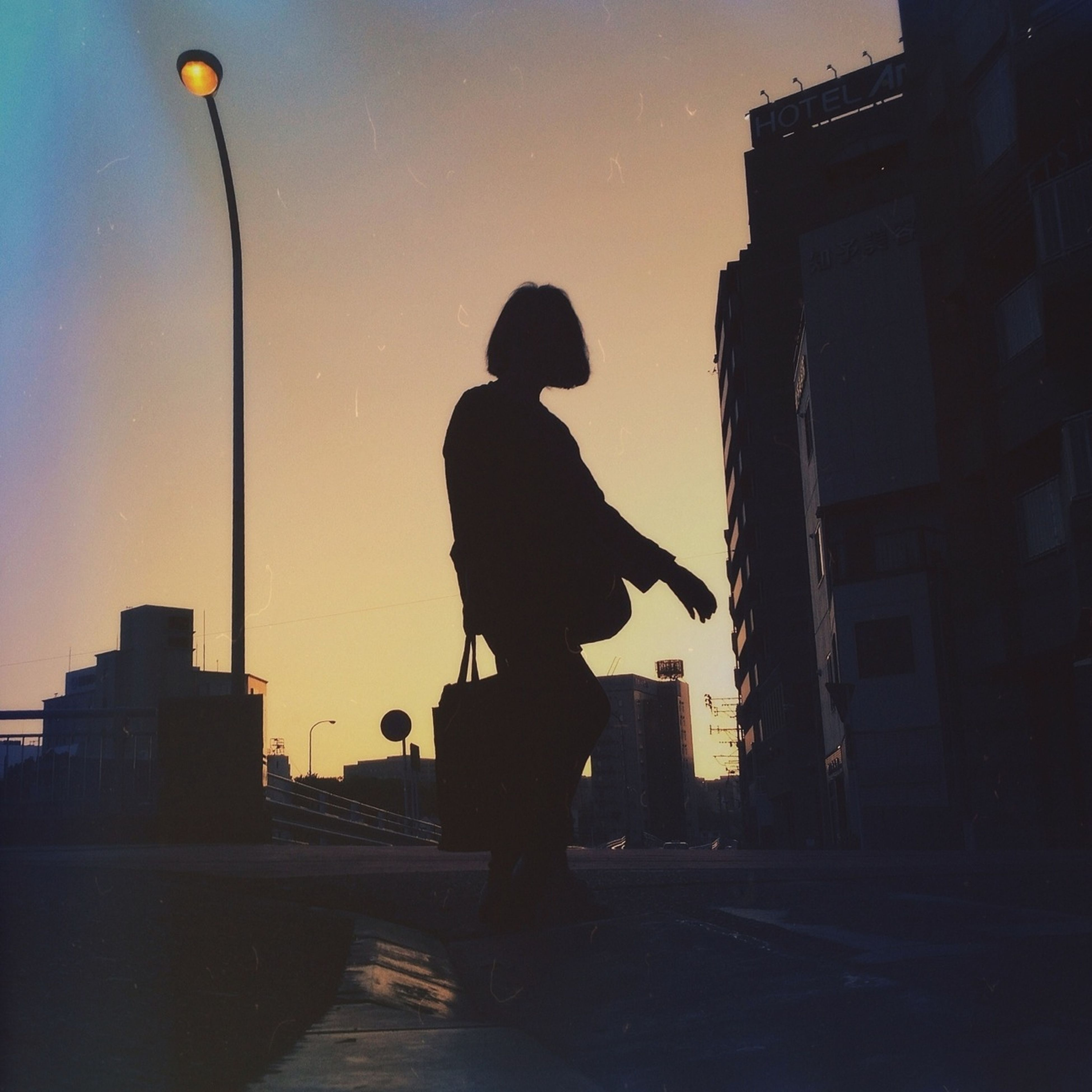full length, silhouette, lifestyles, men, built structure, building exterior, leisure activity, rear view, architecture, walking, sky, street, standing, sunset, street light, low angle view, city