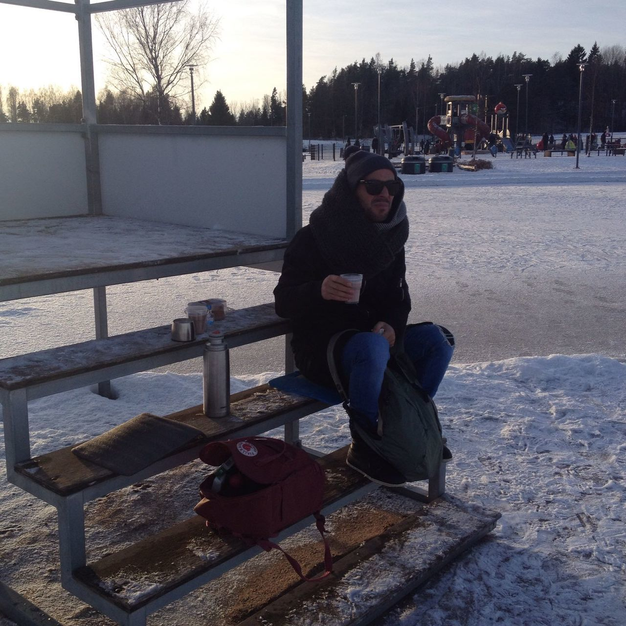 Full Length Of Man Holding Tea While Sitting On Steps During Winter