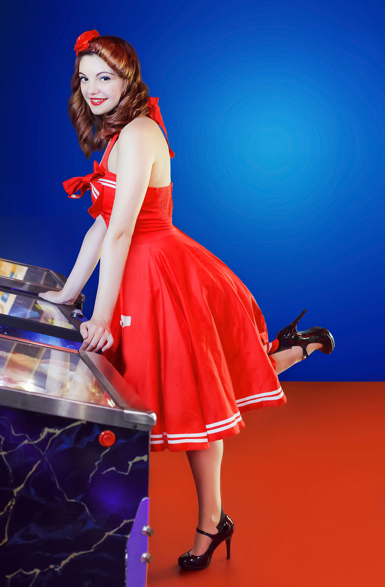 Girl in red dress pin up style, play pinball. Light blue background with space for additional text. Blue Background Fashion Flipper Hobbies Looking At Camera Pin-Up Photo Shoot Playing Games Portrait Red Dress Vintage Women Young Adult Young Women