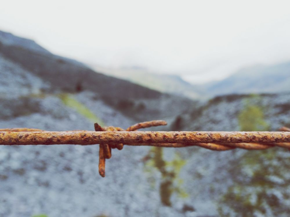 Rusty metal barbed wire line. Focus On Foreground Day Mountain Nature No People Rusty Outdoors Close-up Sky Beauty In Nature Barbed Wire Rust Old LINE Lines Wire Rusty Wire Historic Abandoned Abandoned Buildings Remote