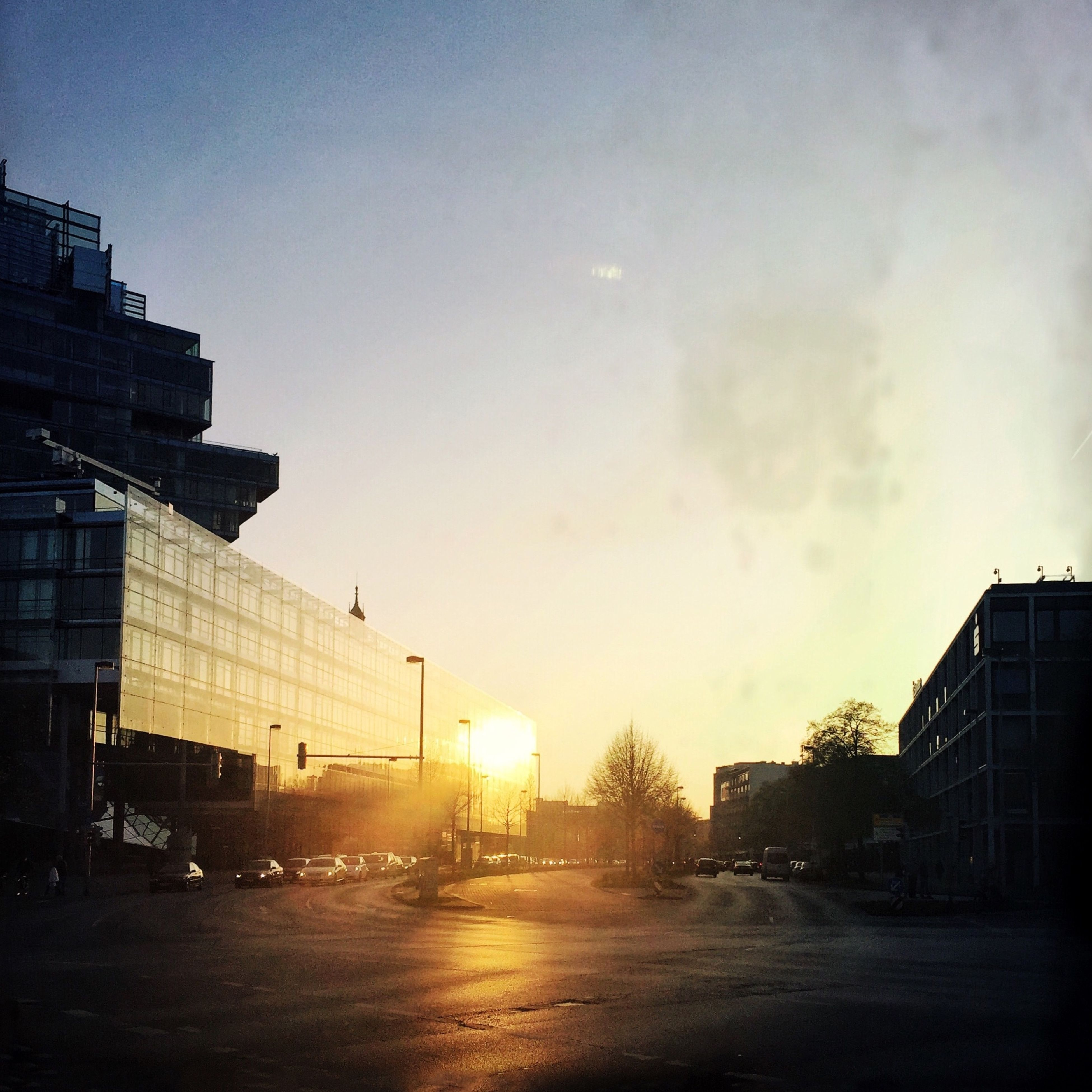 building exterior, architecture, built structure, sun, sunset, sky, city, street, sunlight, road, building, lens flare, car, sunbeam, transportation, silhouette, residential building, street light, outdoors, residential structure