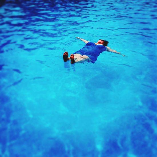 Auntie Karen floating in the pool. Swimming Pool Plussize Woman Summer Blue Bathingsuit