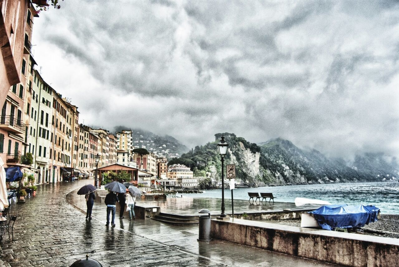 People Walking On Street Amidst Building And Sea Against Cloudy Sky During Monsoon