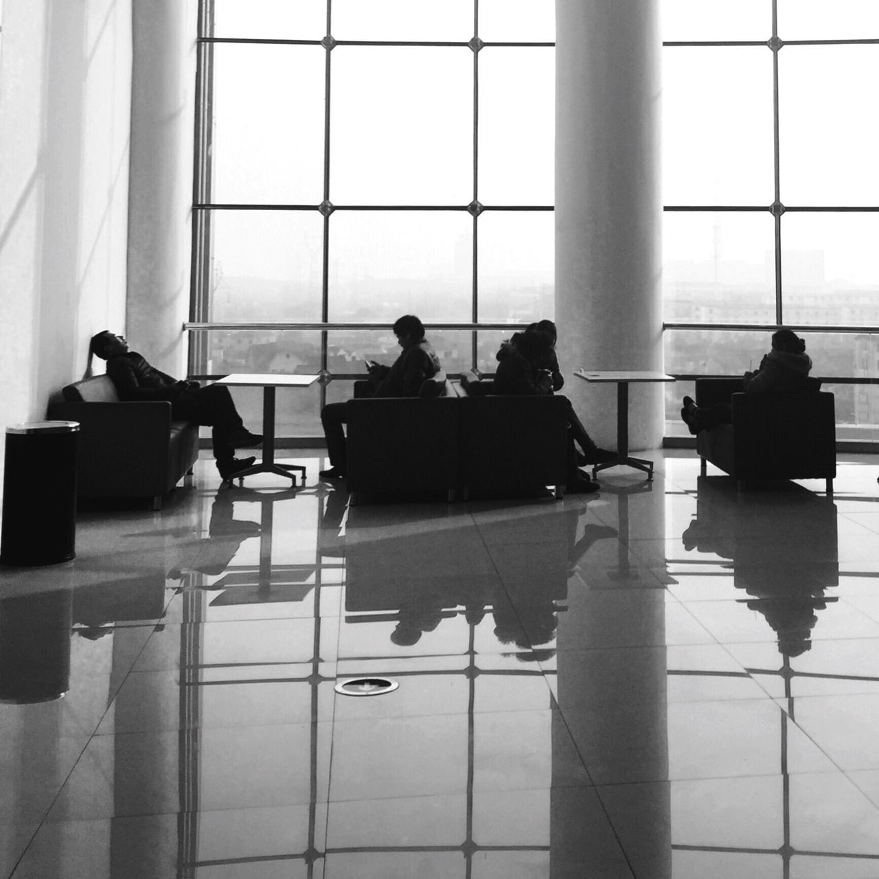 window, indoors, reflection, sitting, real people, table, chair, men, day, silhouette, architectural column, architecture, built structure, women, airport departure area, people