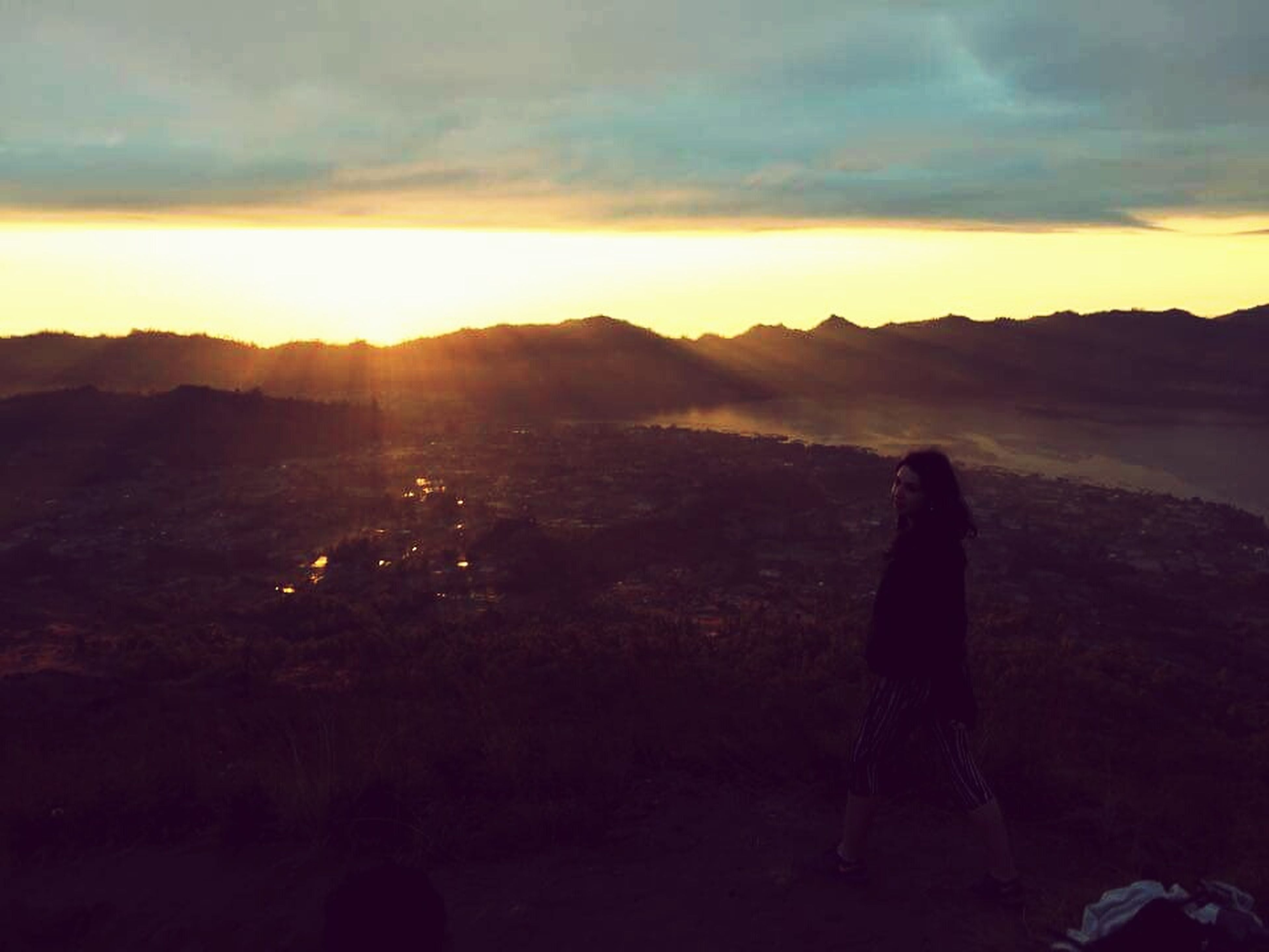 sunset, silhouette, sky, mountain, cloud - sky, scenics, tranquil scene, lifestyles, standing, men, beauty in nature, tranquility, leisure activity, landscape, nature, person, rock - object, sun