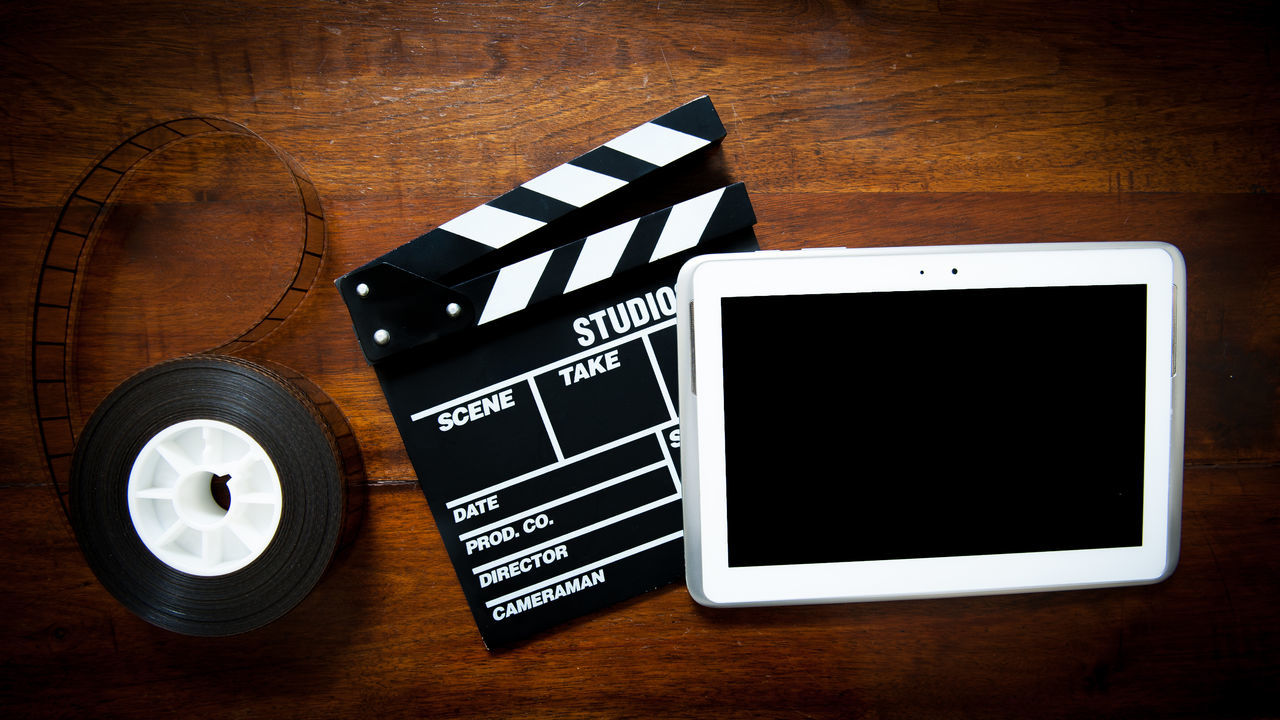 Scriptwriter desktop with tablet and movie objects Arts Culture And Entertainment Author Cinema Clapper Clapper Board Close-up Day Desktop Film Industry Filmstrips Indoors  MOVIE No People Reel Screenwriting Scriptwriting Tablet Technology Wood - Material