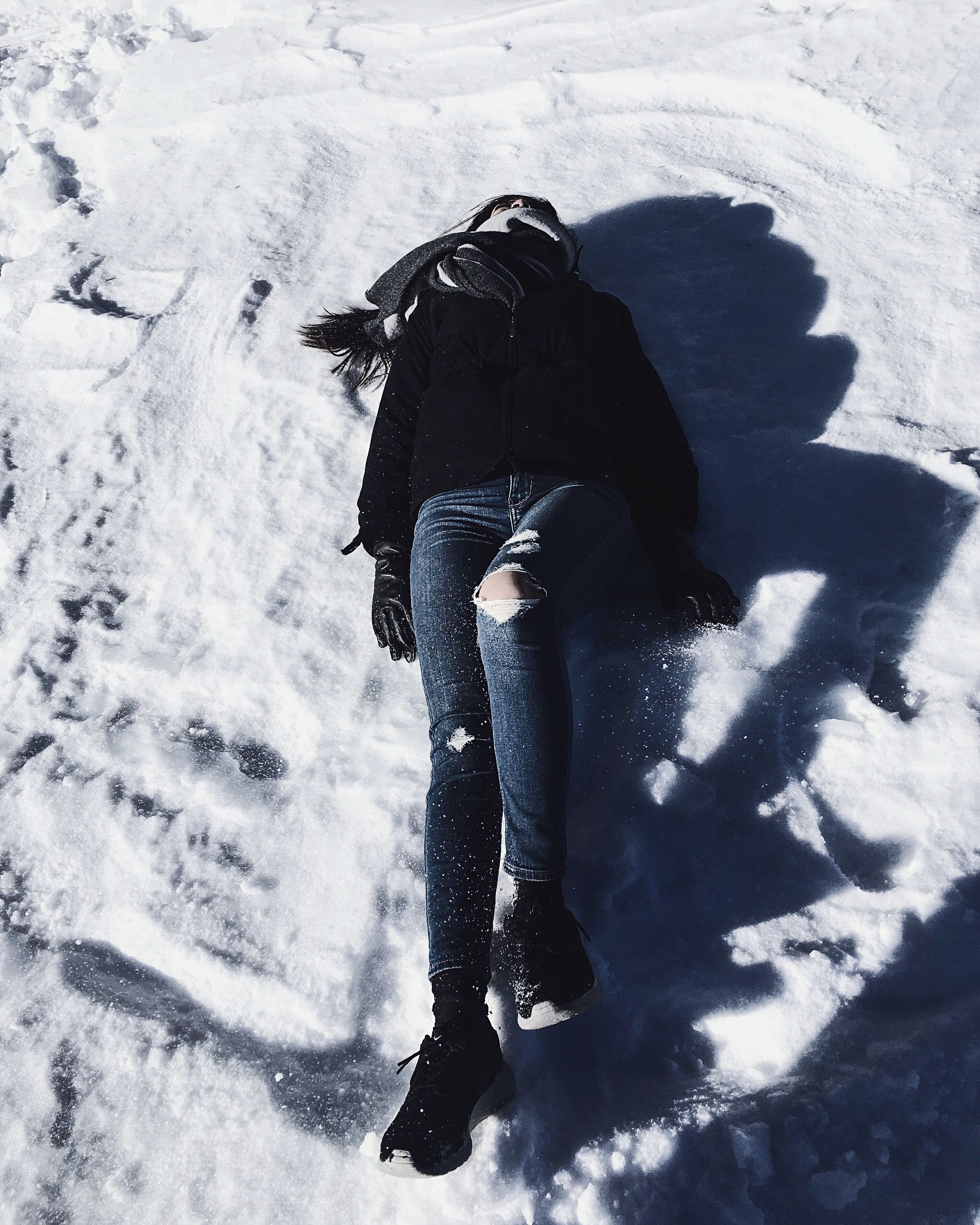 lifestyles, leisure activity, winter, snow, high angle view, cold temperature, full length, standing, shadow, season, warm clothing, sunlight, three quarter length, outdoors, day, weather, casual clothing, young adult