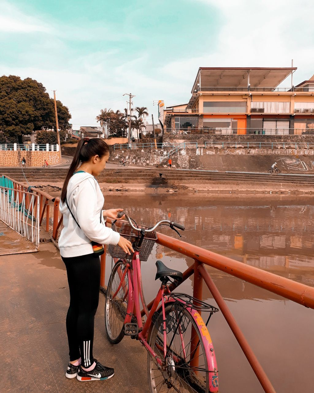 real people, full length, one person, bicycle, lifestyles, casual clothing, building exterior, young adult, young women, built structure, architecture, outdoors, side view, land vehicle, leisure activity, transportation, mode of transport, sky, day, bridge - man made structure, standing, city