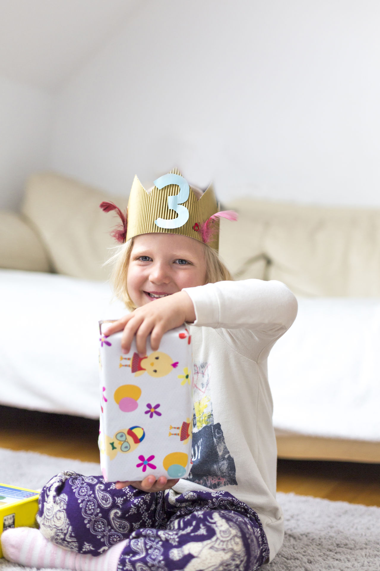 Portrait of adorable child with crown and birthday presents 3 4 Adorable At Home Birthday Birthday Party Blonde Celebrating Childhood Crown Girl Happiness Happy Joy Lifestyles Playing Presents Princess Queen Selfmade Sitting Smiling Sofa Toddler  Unboxing
