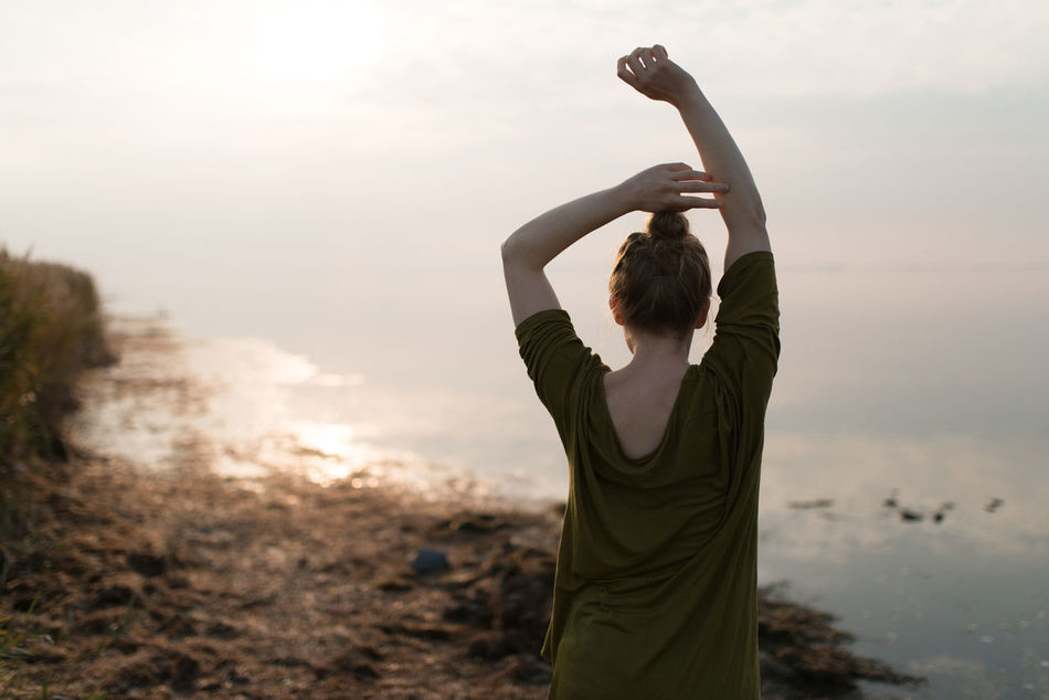 Adult Adults Only Arms Raised Athlete Day Exercising Grass Hand Raised Healthy Lifestyle Human Arm Human Body Part Landscape Nature One Person One Young Woman Only Only Women Outdoors People Sky Stretching Sunset Young Adult Young Women