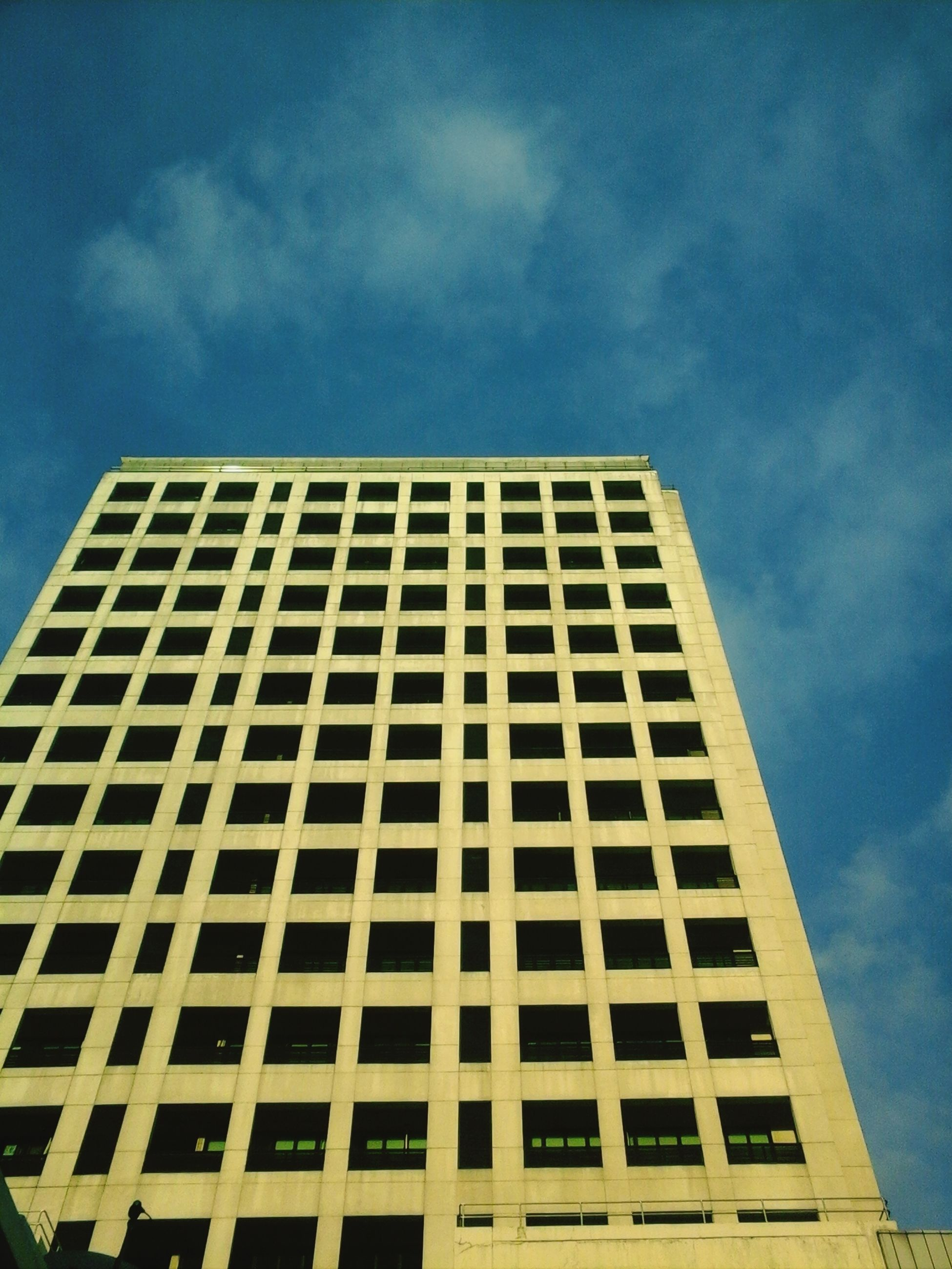 architecture, low angle view, building exterior, built structure, sky, modern, office building, window, city, building, glass - material, tall - high, cloud - sky, tower, skyscraper, day, reflection, outdoors, cloud, blue