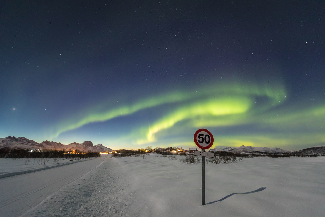Northern Lights above an empty road and speed limit road sign near Holmstad, Vesterålen Astronomy Atmospheric Mood Aurora Borealis Aurora Polaris Beauty In Nature Cold Temperature Dramatic Sky Empty Road Green Color Illuminated Light - Natural Phenomenon Lofoten And Vesteral Islands Motion Mountain Range Natural Phenomenon Night Number 50 Remote Road Sign Scenics Snow Space And Astronomy Speed Limit Sign Star - Space Winter