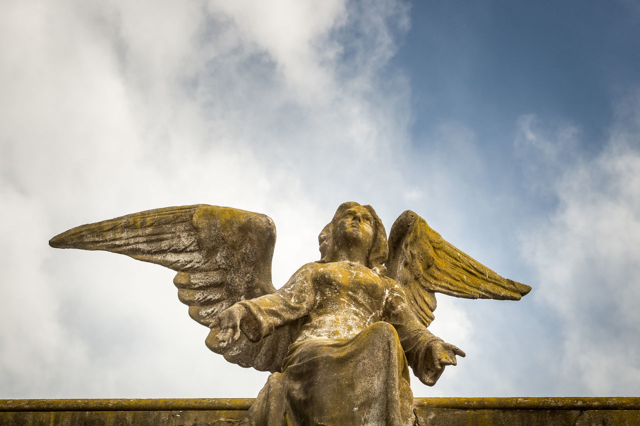 Low Angle View Of Old Angel Statue Against Sky