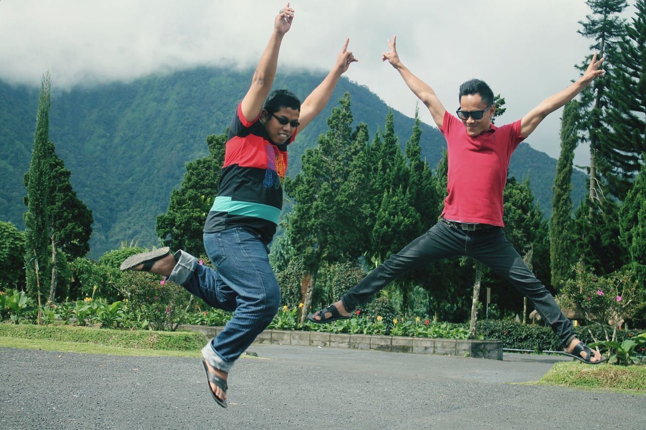 full length, casual clothing, mid-air, day, two people, jumping, leisure activity, front view, outdoors, tree, togetherness, motion, real people, energetic, childhood, nature, sky