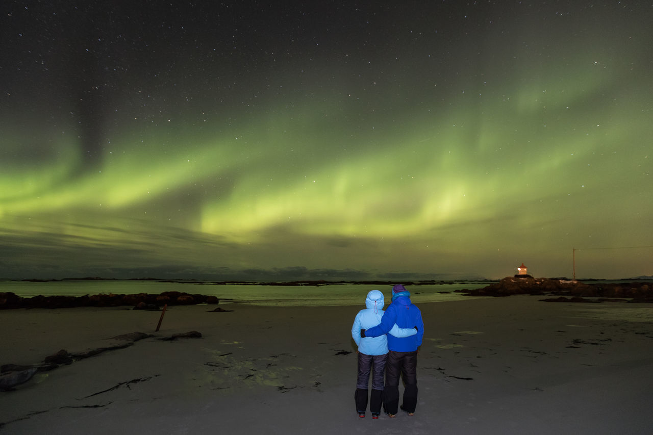 Couple standing on beach under sky illuminated by aurora borealis Adult Astronomy Atmospheric Mood Aurora Borealis Aurora Polaris Beach Beauty In Nature Cold Temperature Dramatic Sky Full Length Green Color Idyllic Illuminated Lighthouse Lofoten And Vesteral Islands Night People Polar Climate Rear View Scenics Sea Sky Space And Astronomy Star - Space Togetherness