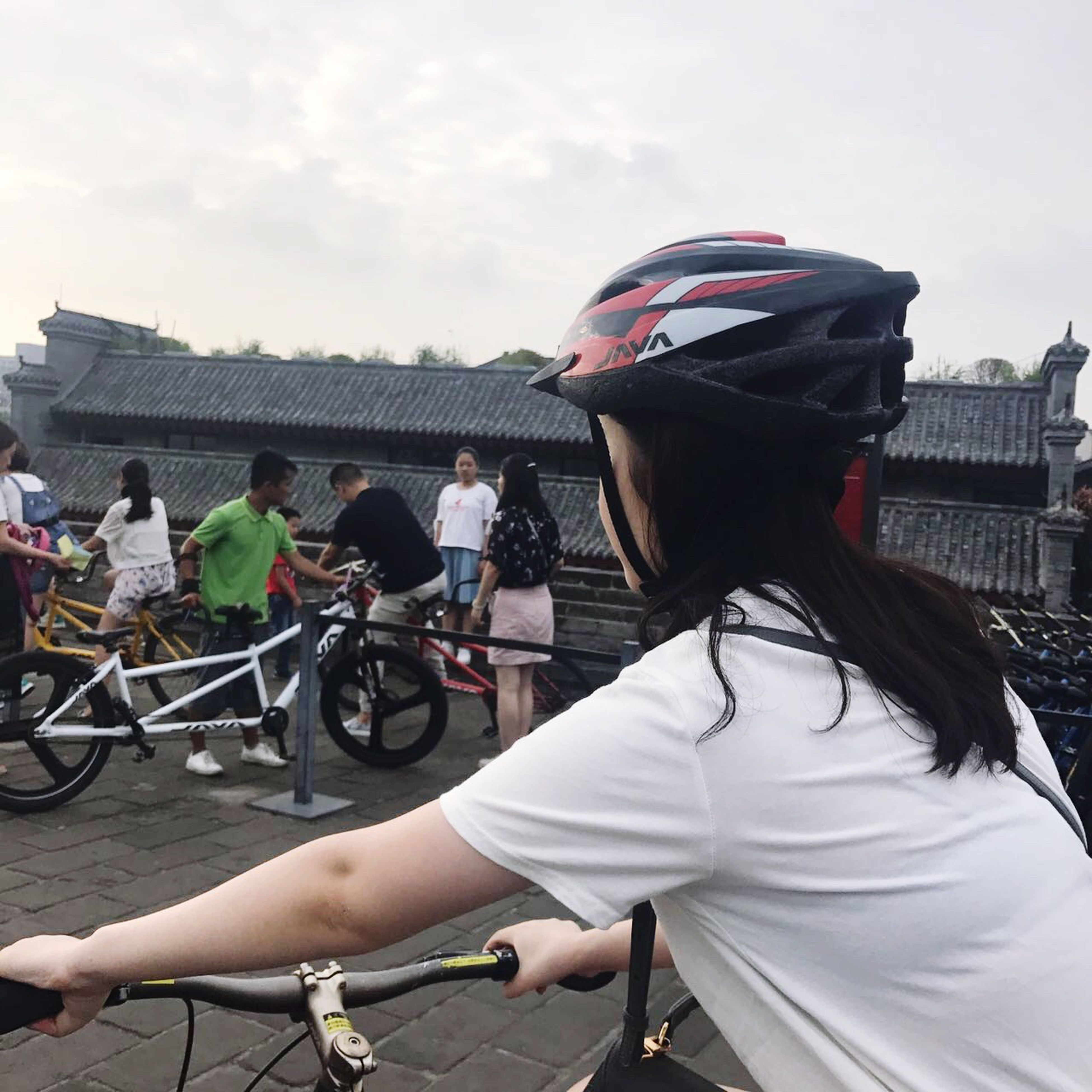 bicycle, real people, lifestyles, cycling, transportation, outdoors, leisure activity, mode of transport, women, men, land vehicle, large group of people, riding, built structure, day, sky, architecture, building exterior, helmet, cycling helmet, city, travel destinations