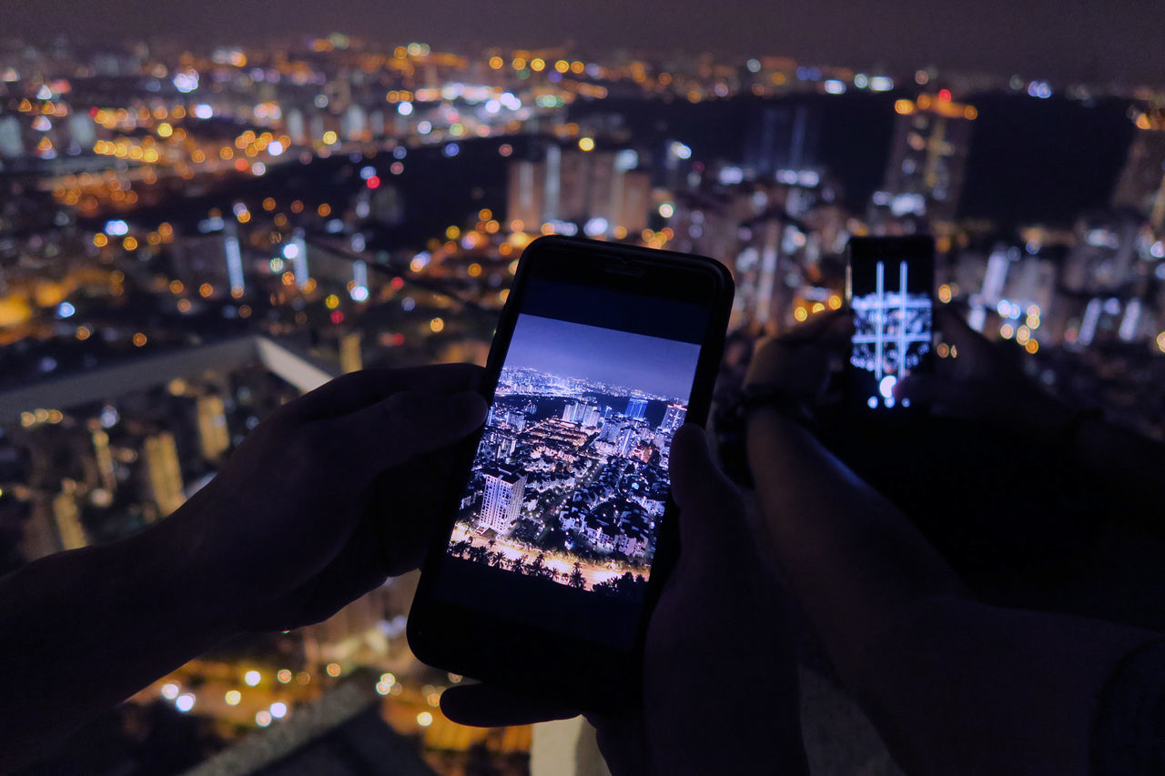 Cropped Image Of Friends Photographing Illuminated Cityscape Through Smart Phone