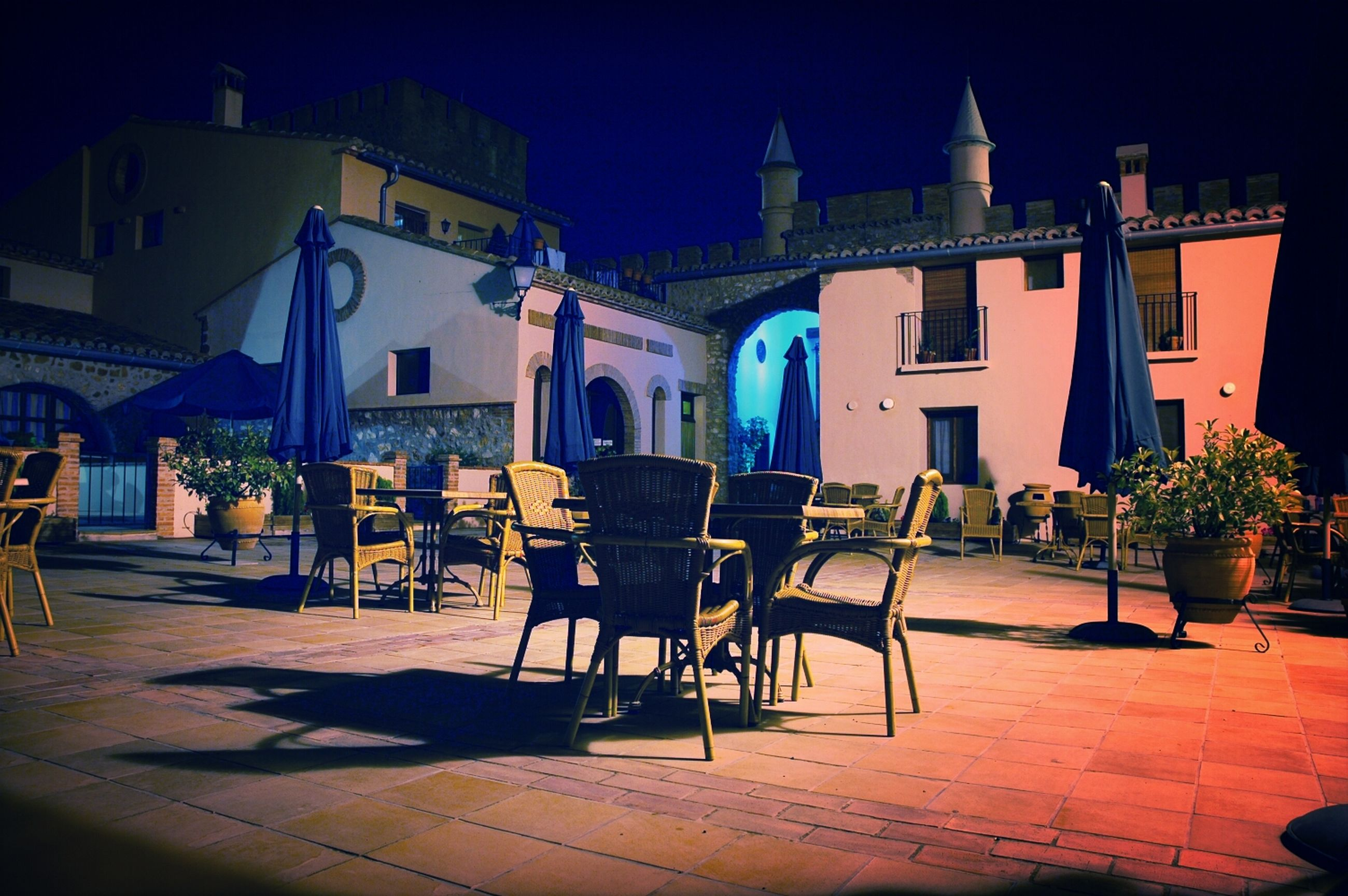 building exterior, architecture, built structure, chair, house, sunlight, residential building, night, residential structure, shadow, table, illuminated, potted plant, city, empty, cobblestone, street light, street, outdoors, blue
