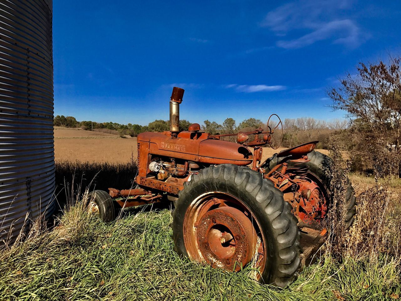 field, agricultural machinery, agriculture, tractor, grass, history, day, rural scene, outdoors, old-fashioned, land vehicle, antique, no people, nature, sky, abandoned, sunlight, transportation, combine harvester, stationary, landscape, tree
