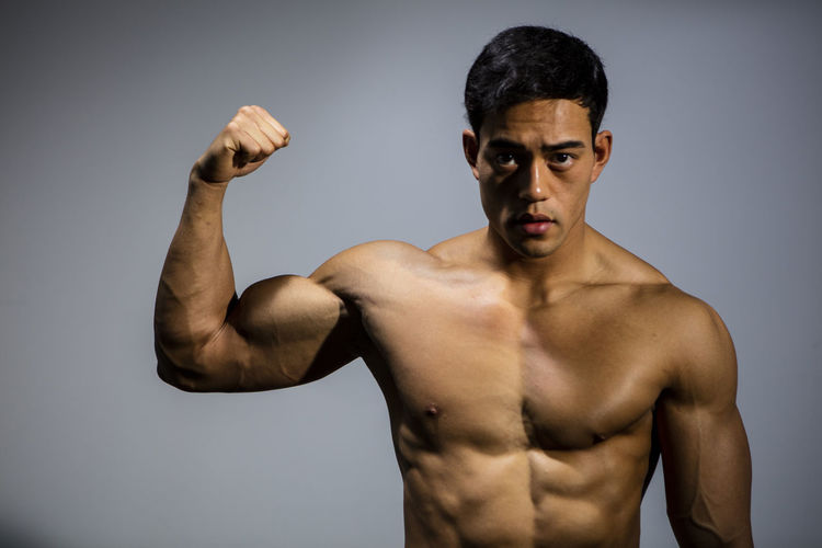 The muscular physique of a male fitness model put on display. The model displays his bicep muscle. Adult Asian  Athletic Body & Fitness Front Facing Human Body Looking At Camera Man Nam Vo Shirtless Vietnamese Bicep Biceps Clenched Fist Fit Fitness Model Flexing Muscles Grey Background Handsome Model Muscles Pectoral Strong Toned Torso
