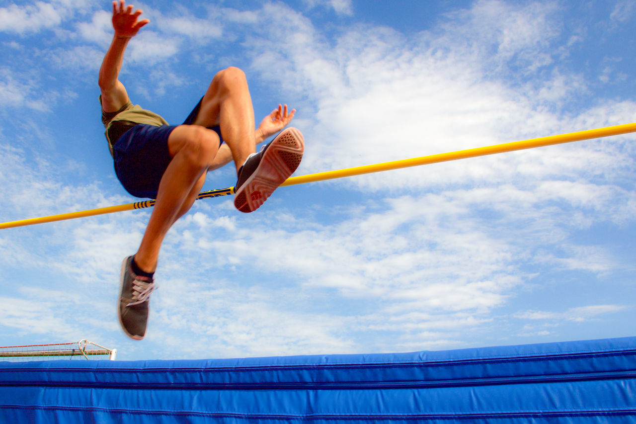 Athlete in a high jump contest caught mid-air from a low angle perspective. Achievement Athlete Clouds And Sky Fosbury Flop High Jump Landing Zone Low Angle Shot Low Angle View Made It Men Mid-air Movement Blur Outdoors Pad Sky Sneakers Sport Sports Sports Event  Sports Photography Success Tension