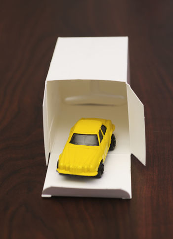 yellow toy car in a cardboard box Box Car Car Model Cardboard Childhood Collection Gift Indoors  Memories Memory Miniature No People Nostalgia Open Box Paper Reminder Surprise Toy Vintage Yellow