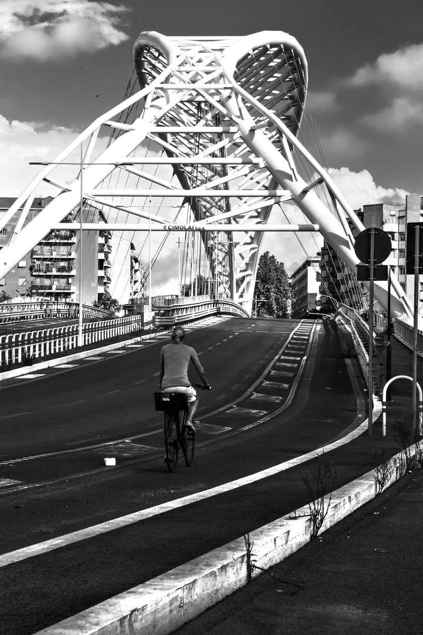 bicycle, cycling, riding, transportation, speed, real people, road, leisure activity, mode of transport, land vehicle, rear view, one person, sky, built structure, outdoors, architecture, motion, day, men, full length, city, people