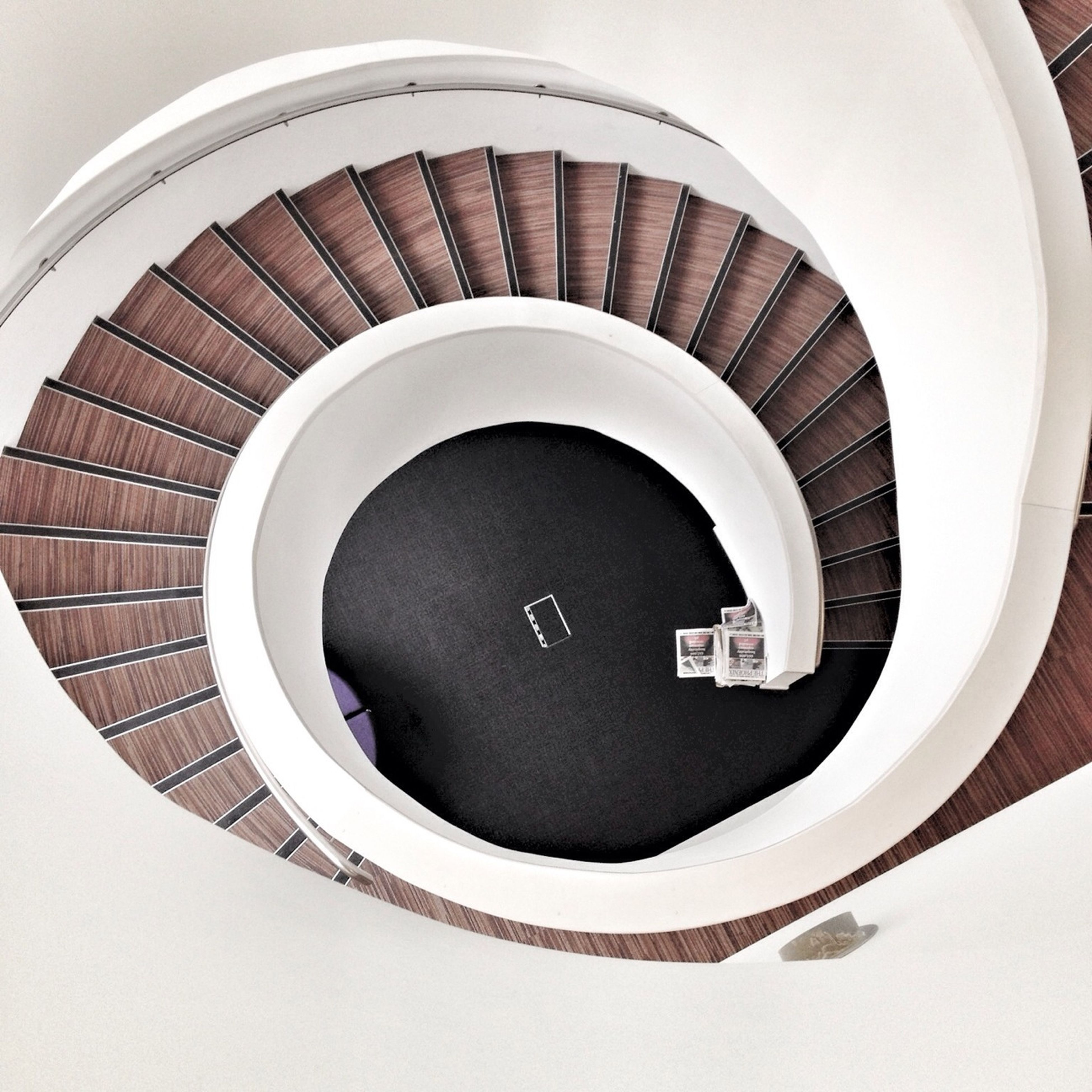 circle, indoors, architecture, built structure, spiral, spiral staircase, steps and staircases, staircase, steps, white color, high angle view, directly above, railing, geometric shape, no people, building exterior, pattern, modern, low angle view, building