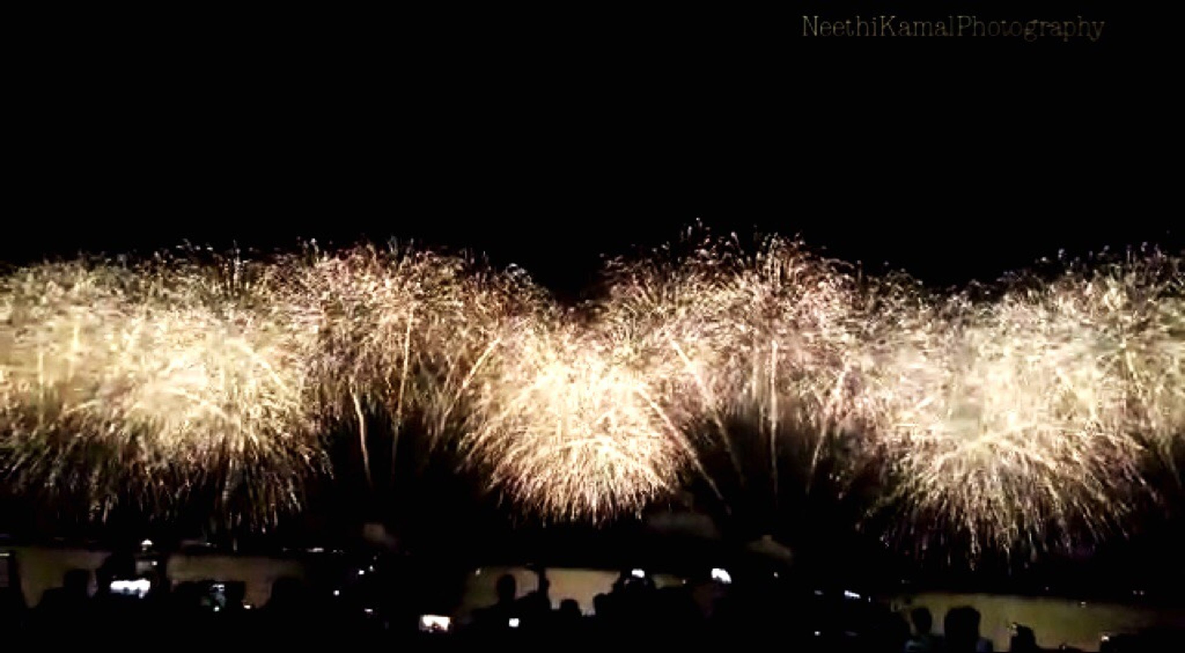 night, illuminated, silhouette, clear sky, dark, arts culture and entertainment, glowing, long exposure, motion, sky, copy space, tree, outdoors, event, light - natural phenomenon, blurred motion, celebration, firework display, low angle view, exploding
