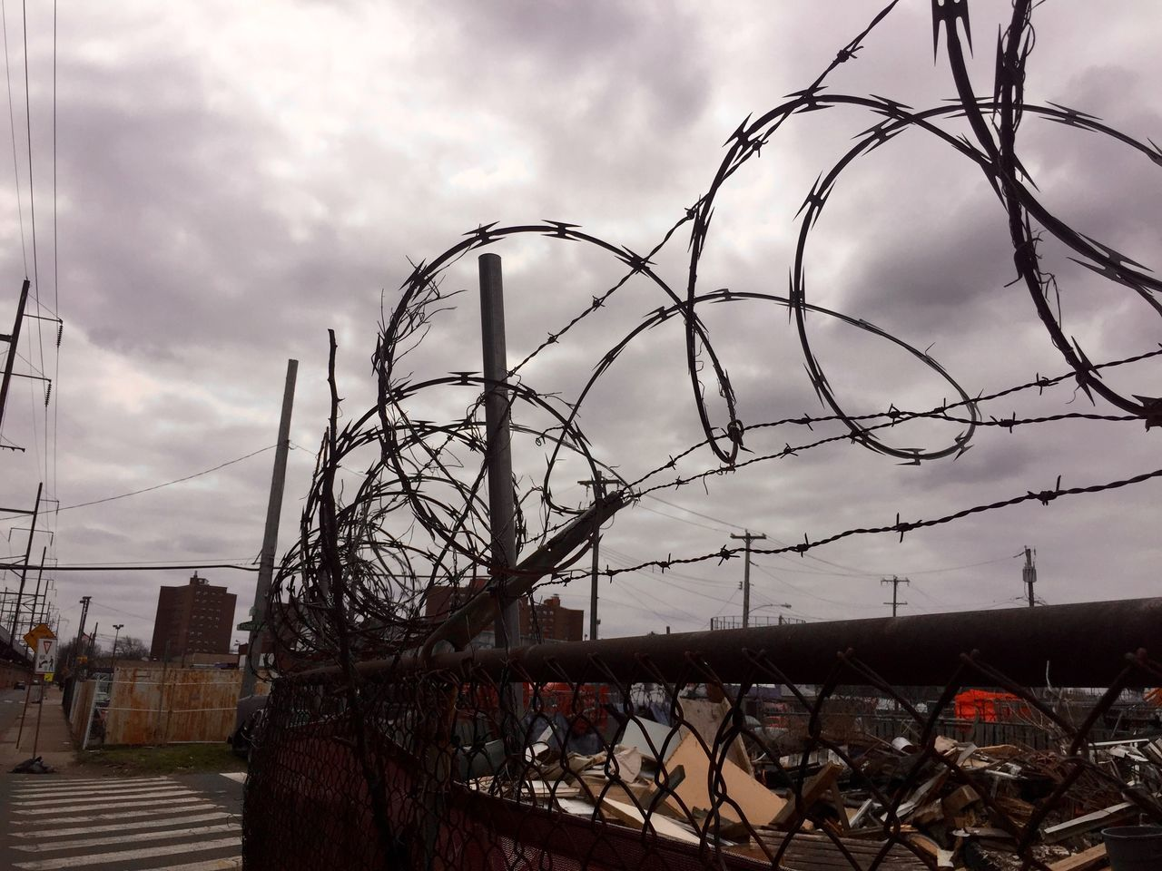 Barbed Wire Chainlink Fence City Cityscape Clouds And Sky Fence Metal Protection Razor Wire Razor Wire Fence Safety Urban Landscape Urbanphotography