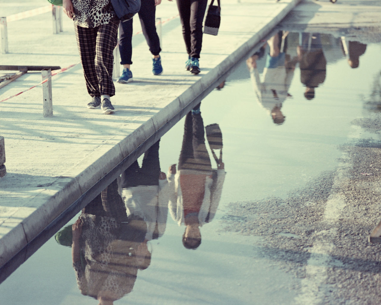 Low Section Of People With Reflection On Water