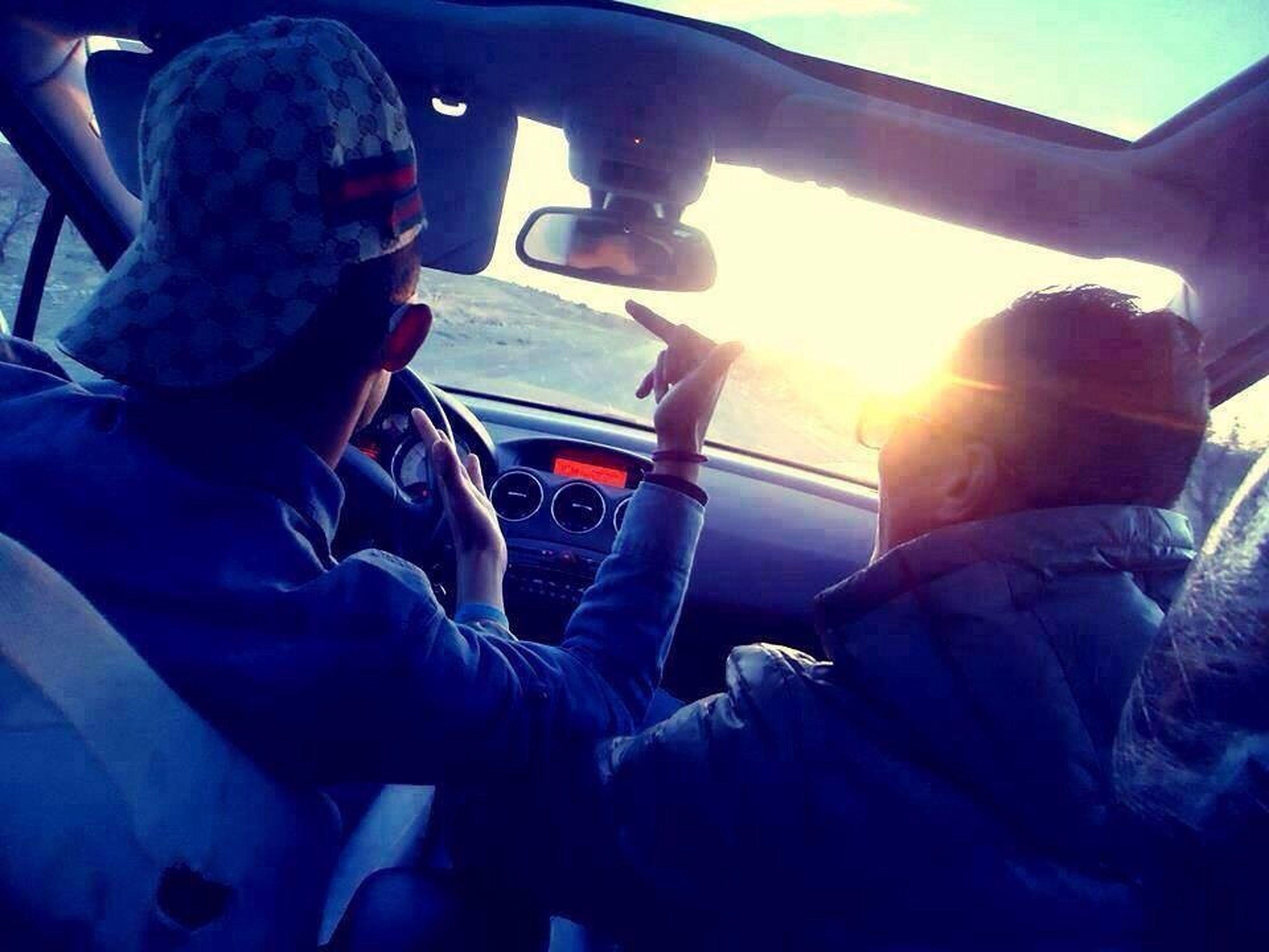 lifestyles, leisure activity, men, transportation, togetherness, sitting, mode of transport, vehicle interior, travel, land vehicle, bonding, sunlight, person, sun, casual clothing, love, journey