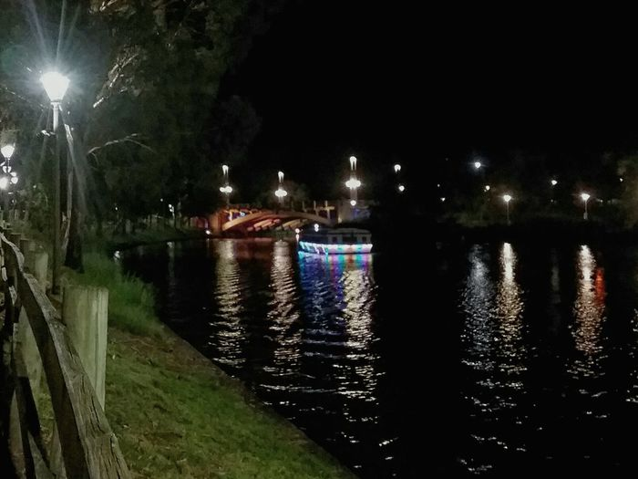 Nightphotography Night Lights Night No People Water Reflections Waterfront Riverside River View River Bank  River Boat Illimunated Boat With Lights Bridge Bridge In Background Lamp Post Trees