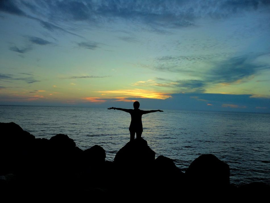Singing the songs of the ocean. Reflection Sunset Nature Sky Silhouette Outdoors Beauty In Nature Travel Travel Destinations Oceanside One Person Shadows & Lights Facing The Ocean Arms Wide Open Silouette & Sky Camiguin Philippines Finding New Frontiers