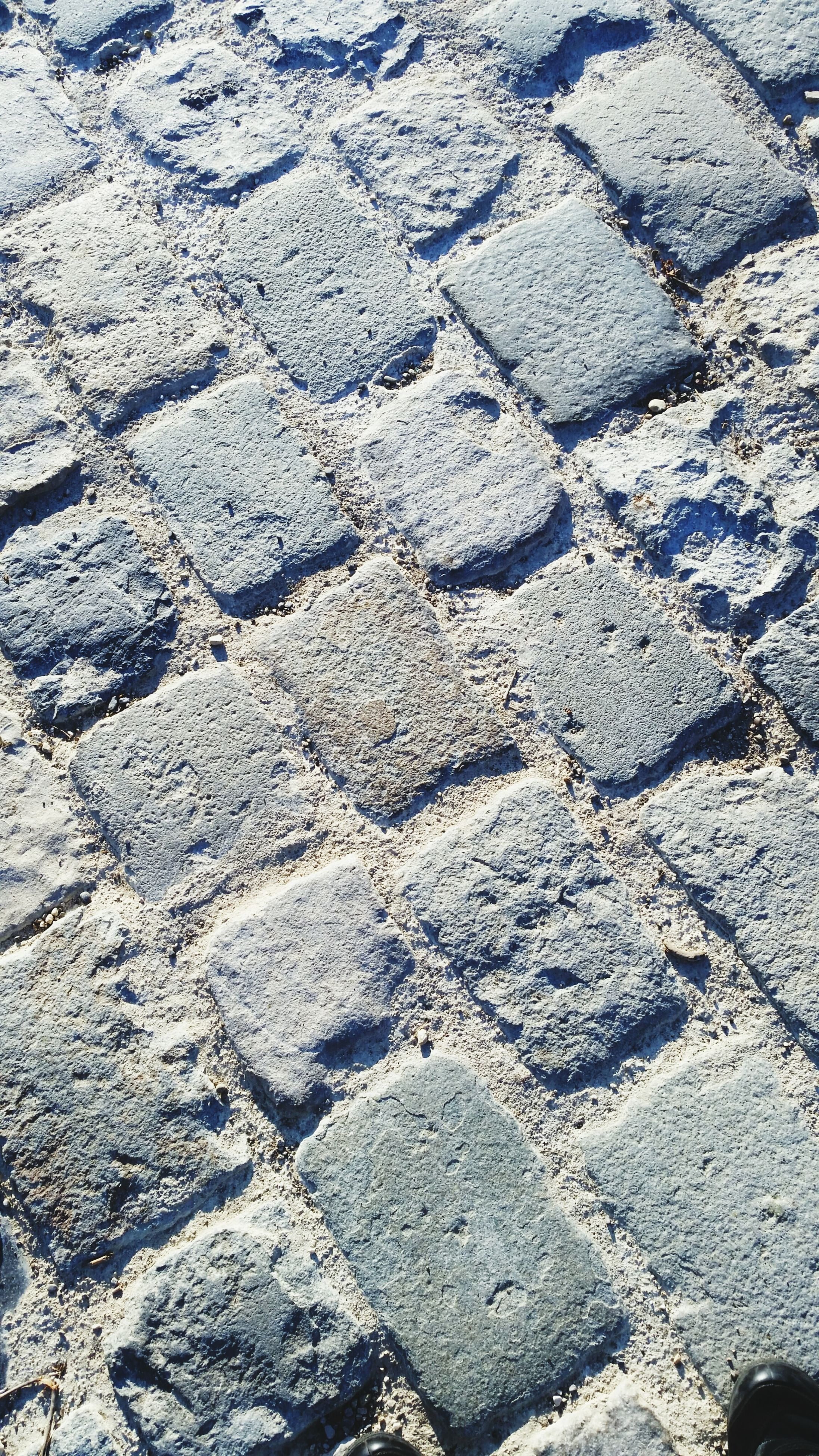 full frame, backgrounds, textured, high angle view, street, pattern, cobblestone, day, asphalt, outdoors, sunlight, no people, rough, road, close-up, stone - object, detail, nature, footpath, elevated view