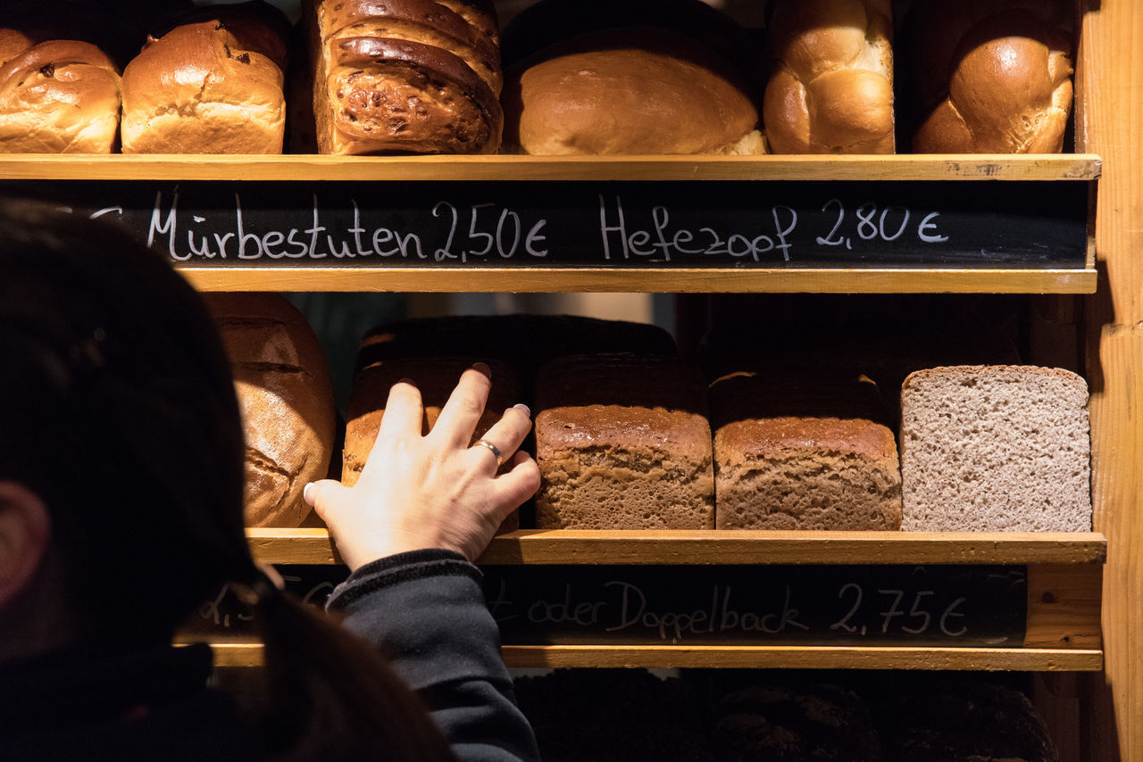 Marktprojekt: Am Backwarenstand Adult Bread Choice Close-up Dark Early Morning Food Hanging Out Horizontal Human Body Part Information Market Stall One Person Open Market Person Price Tag Retail  Selling Bread Selling Food Shelf