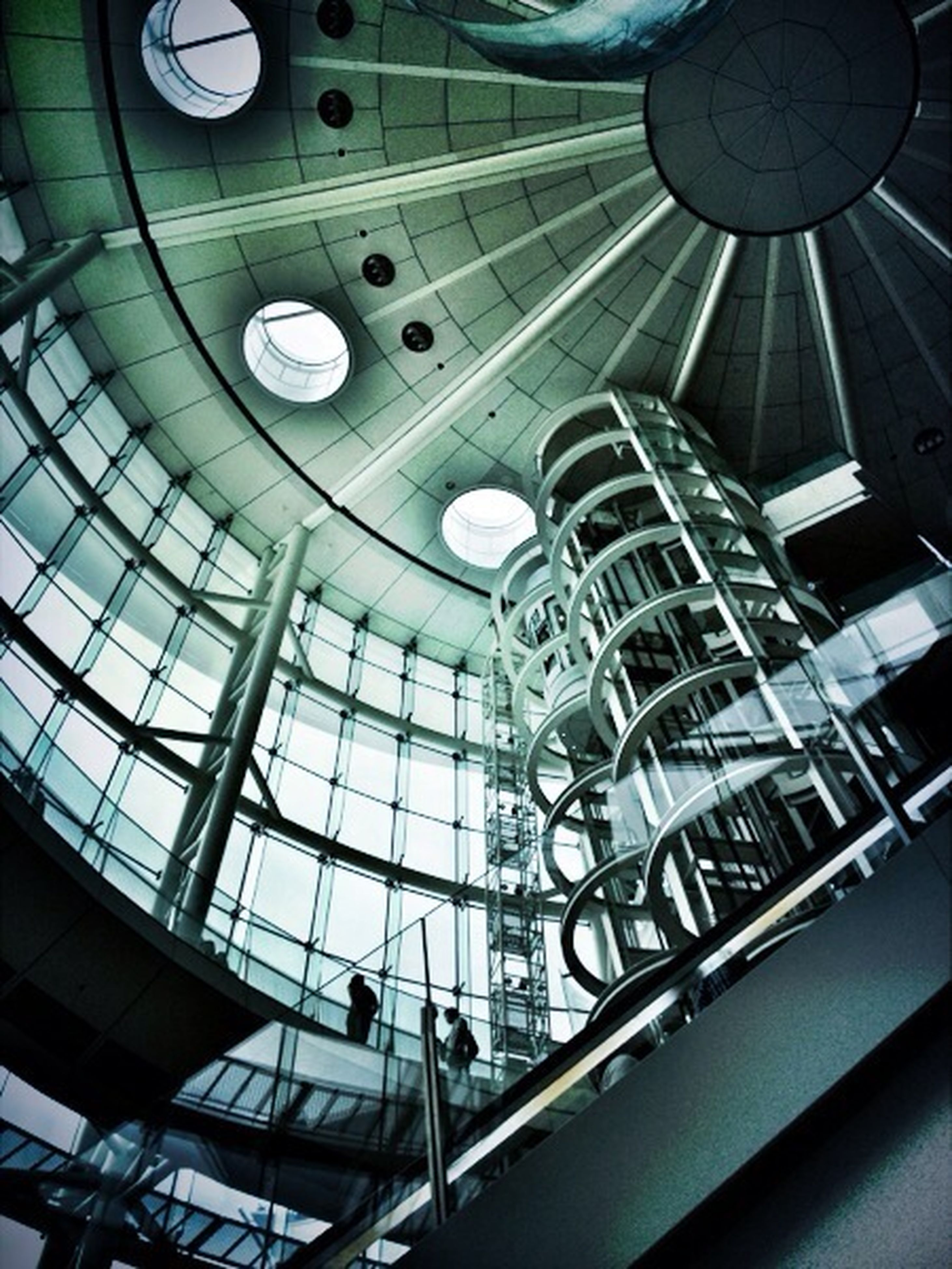 indoors, architecture, low angle view, built structure, ceiling, modern, glass - material, building, skylight, reflection, directly below, window, interior, railing, transparent, architectural feature, no people, day, building exterior, lighting equipment