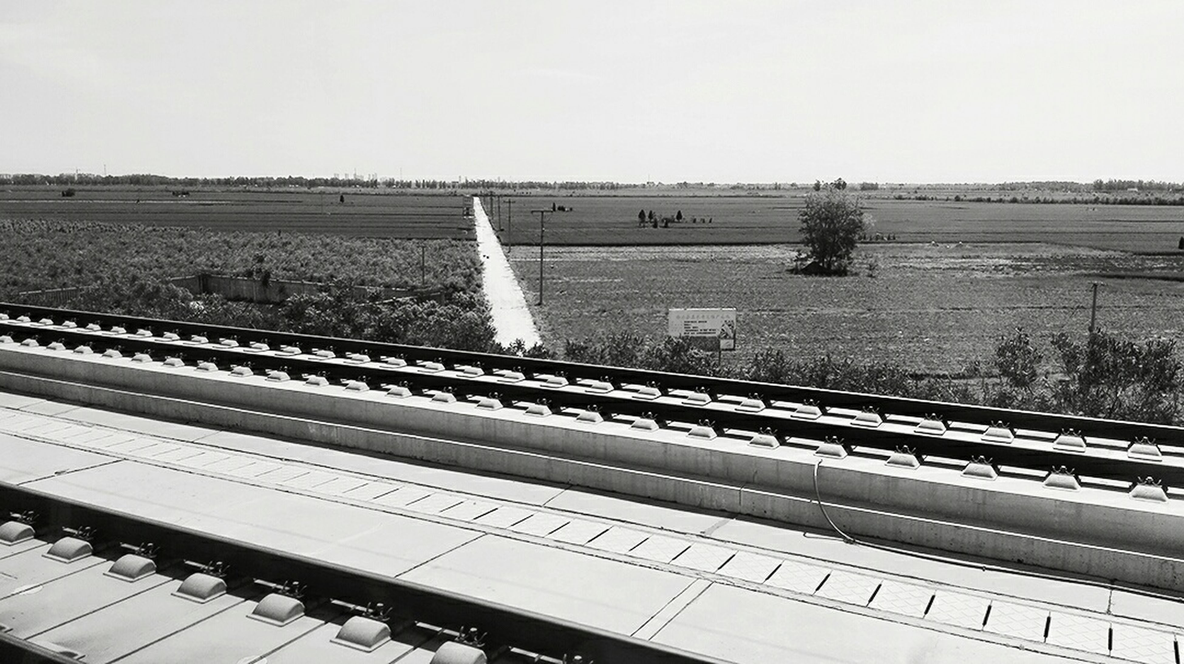 clear sky, field, copy space, agriculture, rural scene, built structure, landscape, growth, railroad track, day, tree, fence, sky, no people, high angle view, farm, architecture, outdoors, nature, building exterior