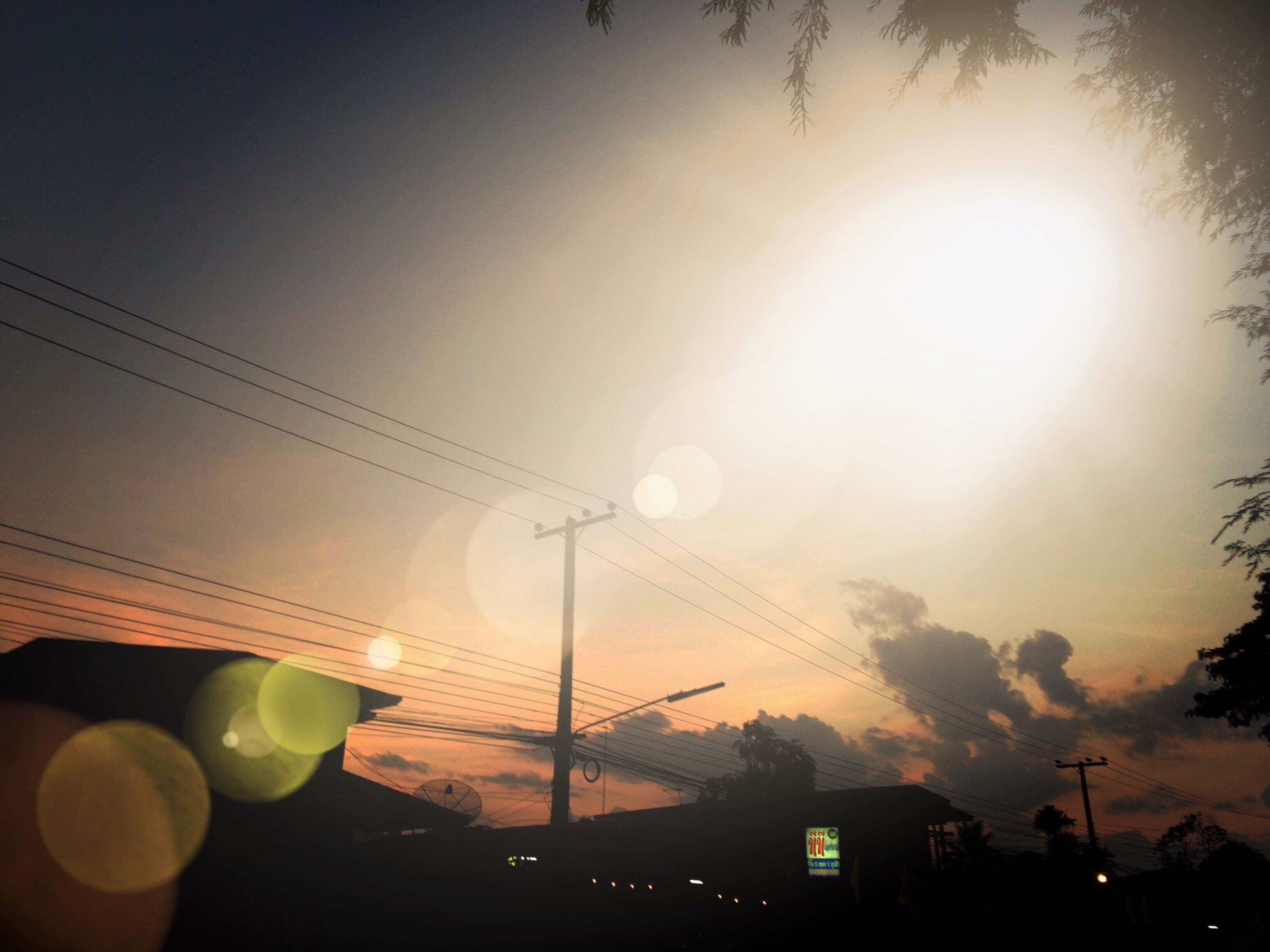 sun, low angle view, electricity, power line, built structure, building exterior, architecture, electricity pylon, lens flare, sky, silhouette, sunset, street light, sunbeam, fuel and power generation, sunlight, power supply, connection, cable, technology