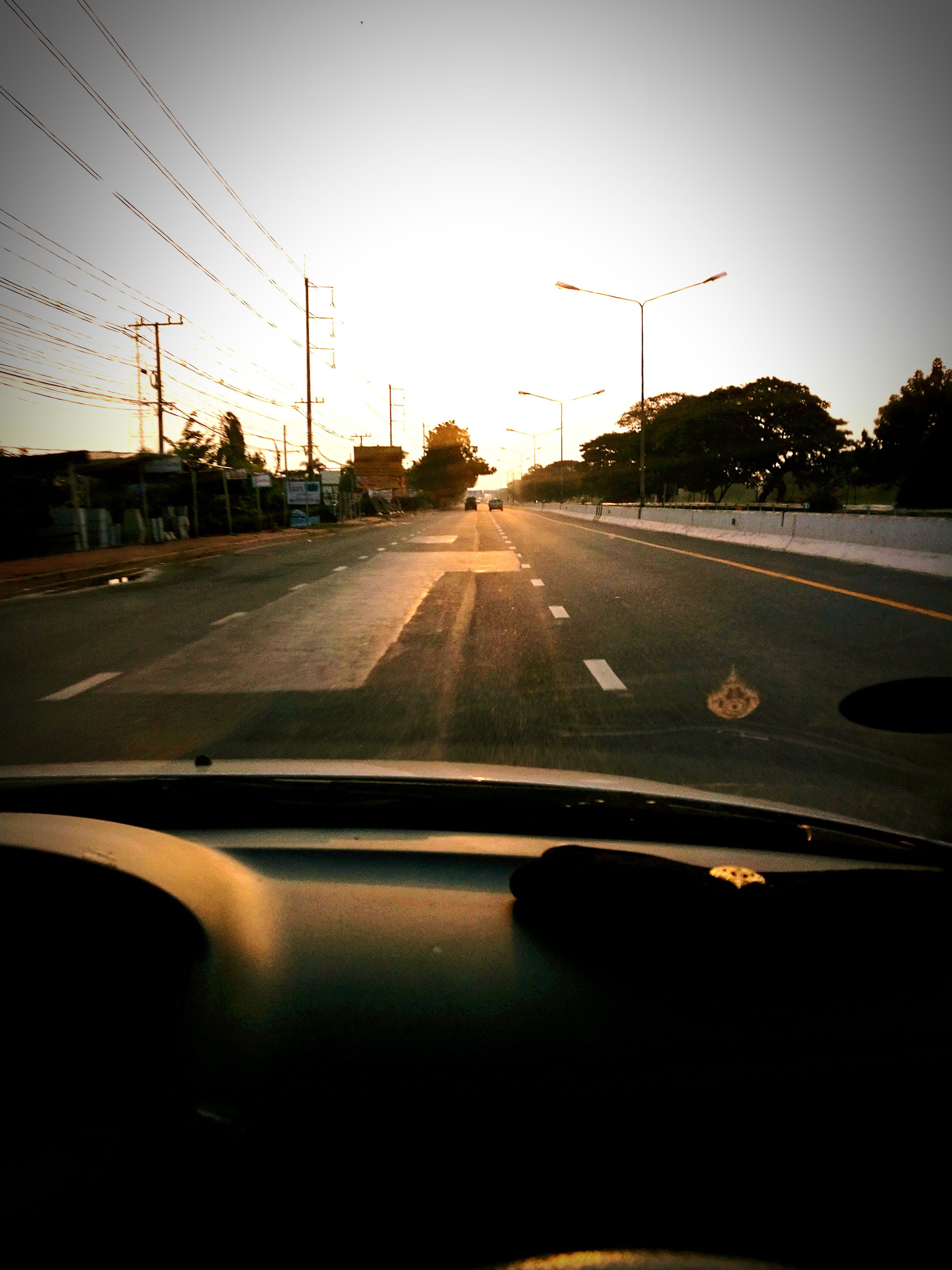 car, transportation, land vehicle, vehicle interior, road, windshield, car interior, mode of transport, car point of view, windscreen, the way forward, driving, sunset, dashboard, no people, sky, day, outdoors