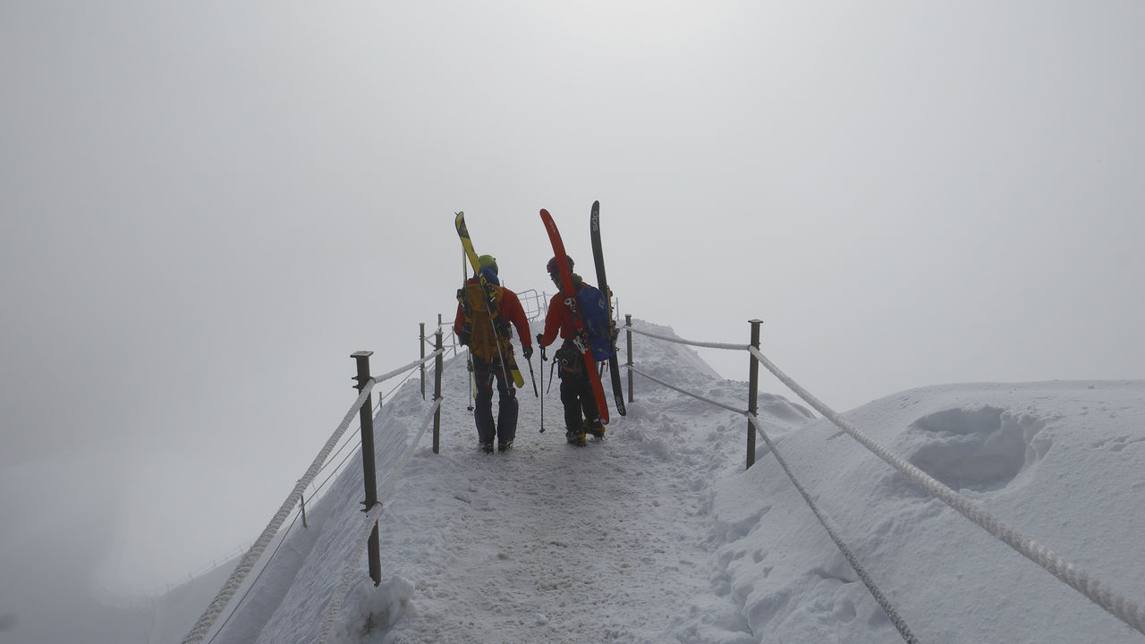 Rear View Of People Walking On Snow At Aiguille Du Midi Mountain