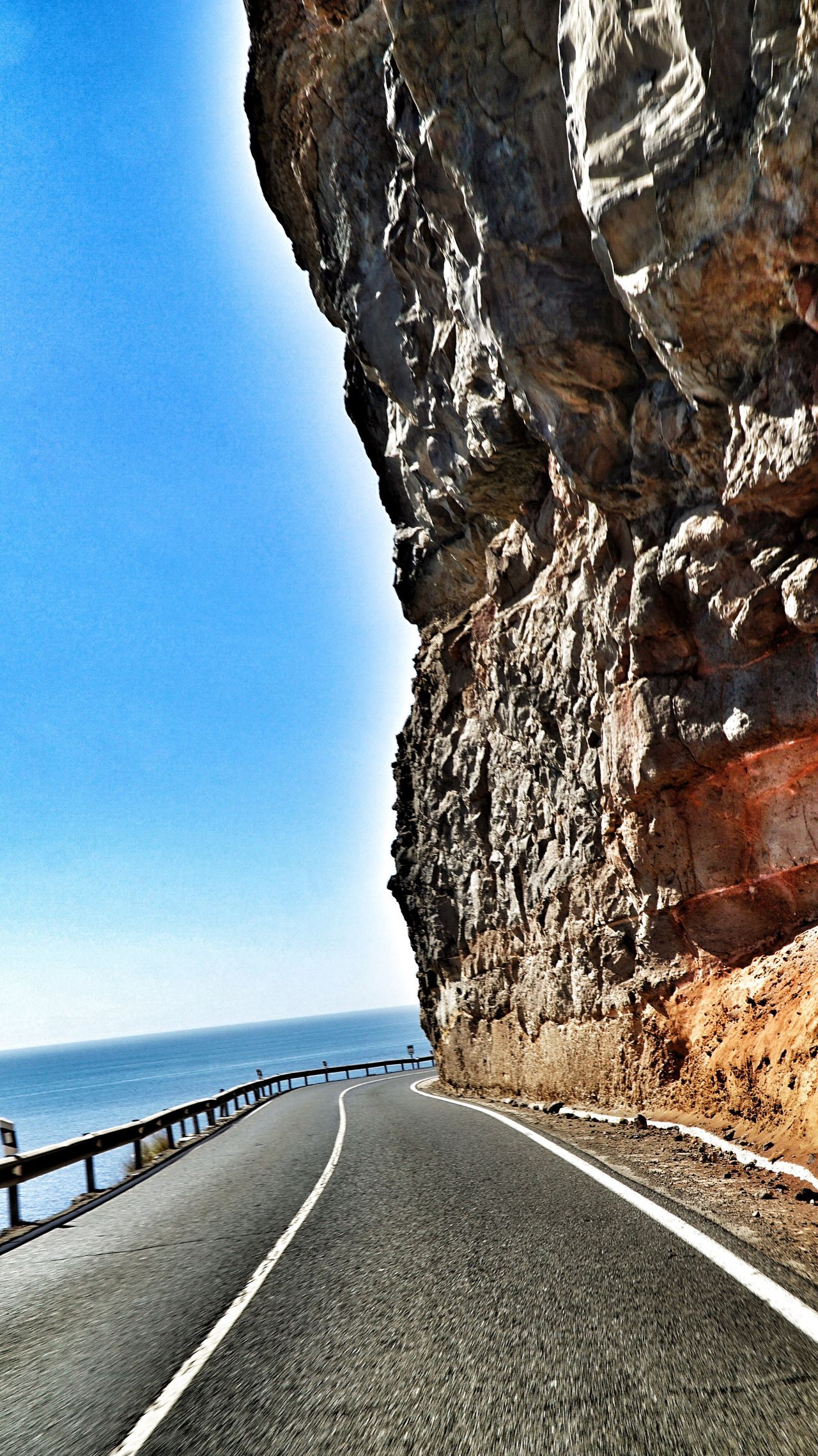 Road The Way Forward Road Transportation Clear Sky Road Marking Blue Tranquil Scene Sea Copy Space Rock - Object Mountain Tranquility Surface Level Day Rocky Mountains Rock Formation Water Scenics Beauty In Nature Outdoors