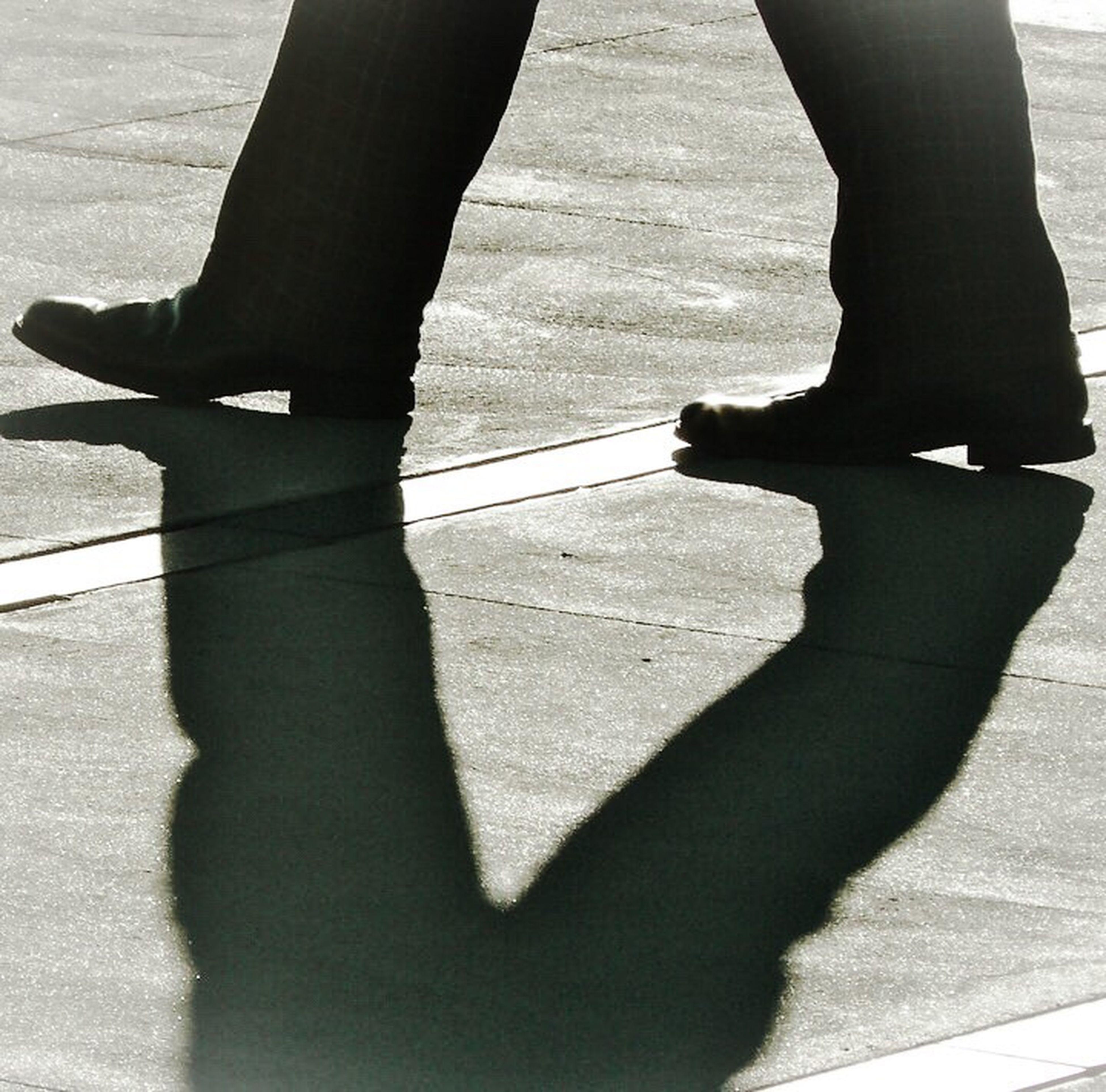 low section, person, lifestyles, standing, shadow, men, human foot, shoe, leisure activity, walking, street, sunlight, focus on shadow, footwear, road
