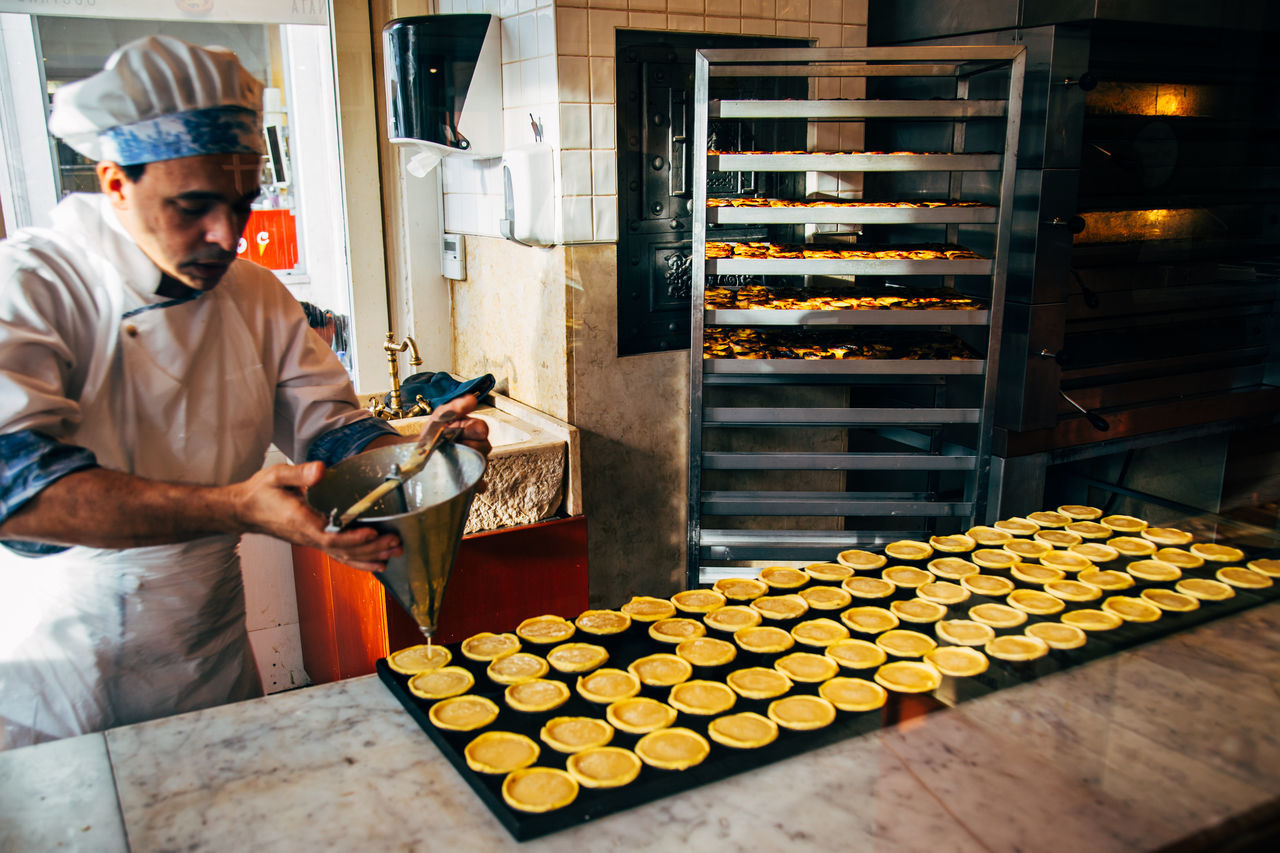 pastry chef filling vanilla custard into pastel de natas Adult Adults Only Baked Goods Baking Custard Delicacy Dessert Indoors  One Man Only One Person Only Men Pastel De Nata Pastry Pastry Chef People Treat Vanilla